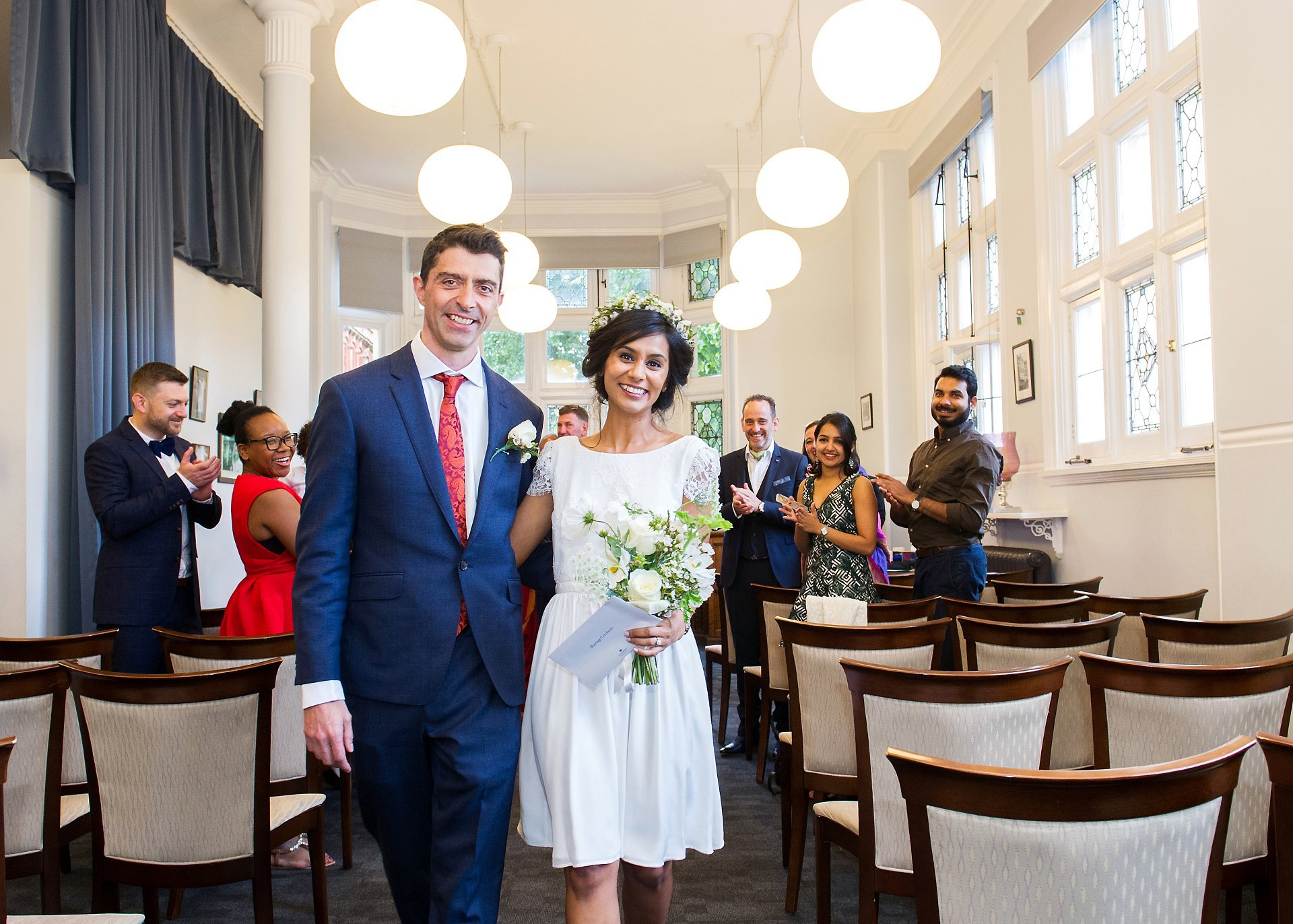 bride and groom leaving ceremony as husband and wife with westminster registrer office wedding photography by emma duggan