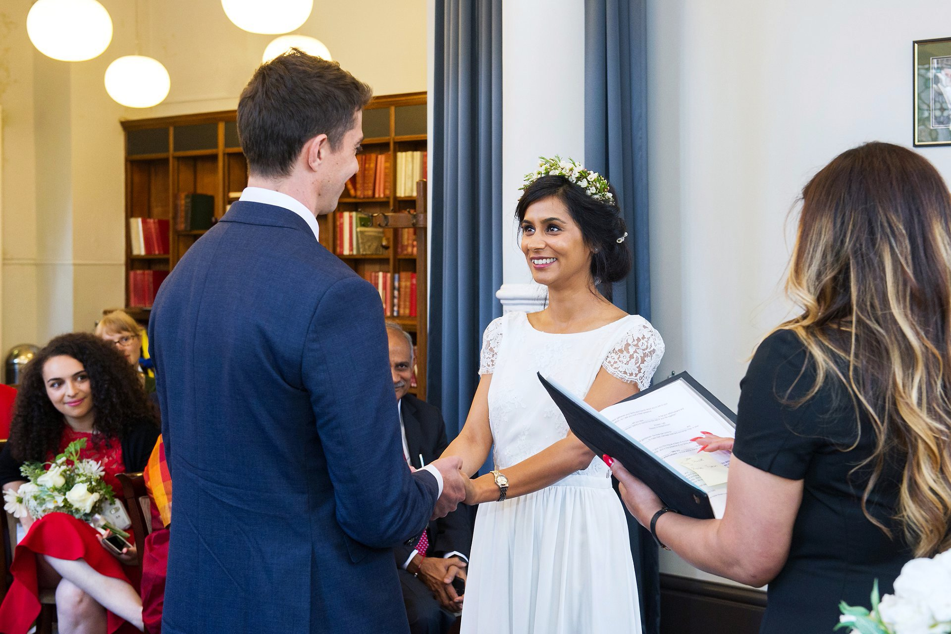 indian bride smiles at her groom during their mayfair room civil ceremony inside mayfair library