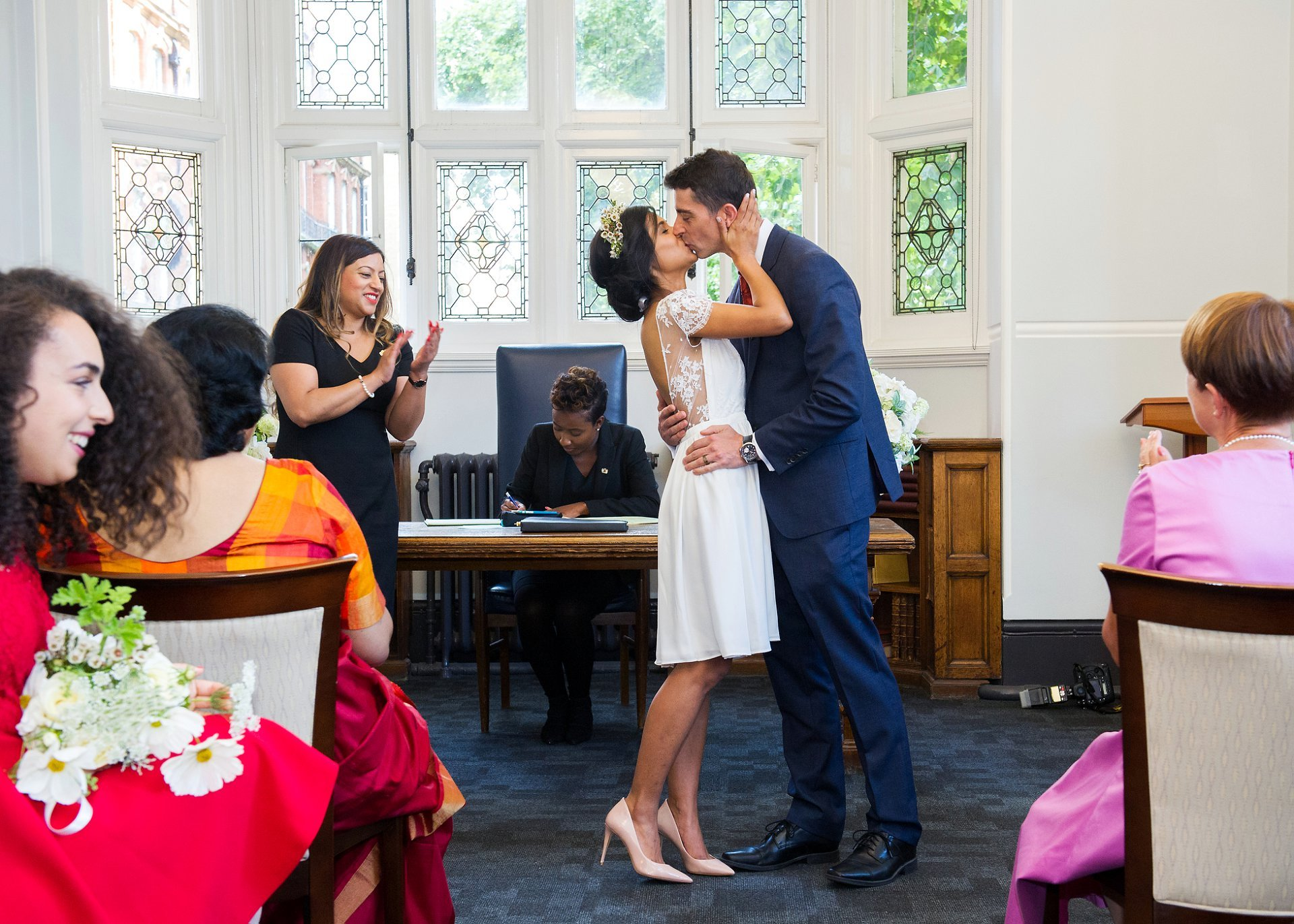 mayfair library summer wedding photography with un streaming into the mayfair ceremony room as the bride and groom kiss for the first time as husband and wife