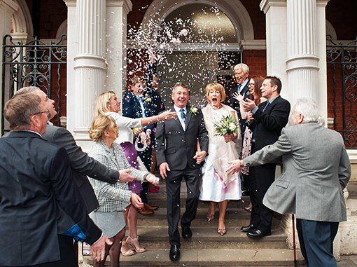 A bride and groom kiss on the steps of Chelsea Old Town Hall while guests throw confetti over them in celebration. Photo: Chelsea Register Office wedding photographer Emma Duggan