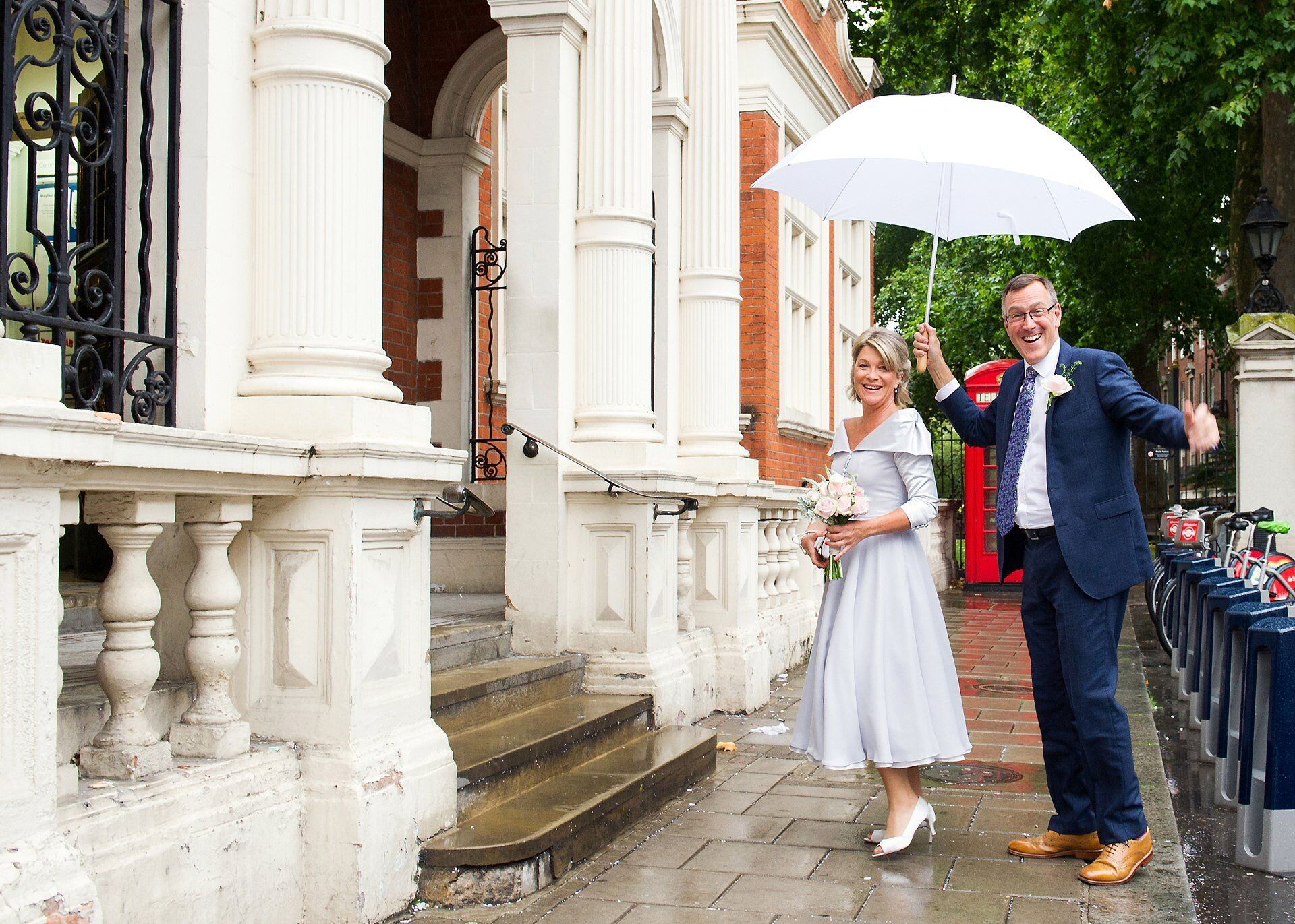 mayfair wedding photographer and a bride and groom arriving in the rain