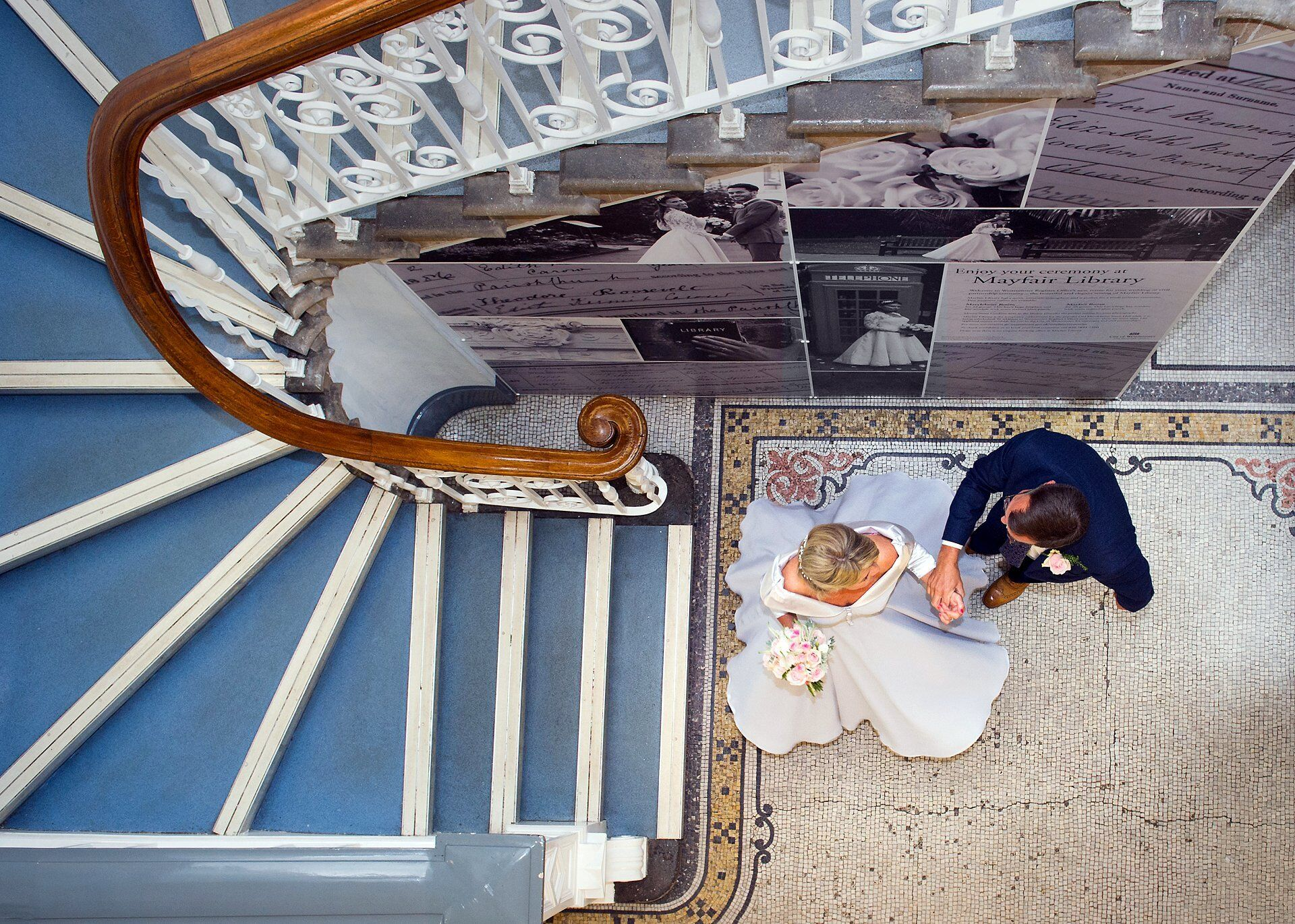 westminster register office wedding photographer emma duggan at mayfair library here a bride and groom twirl at the bottom of the staircase