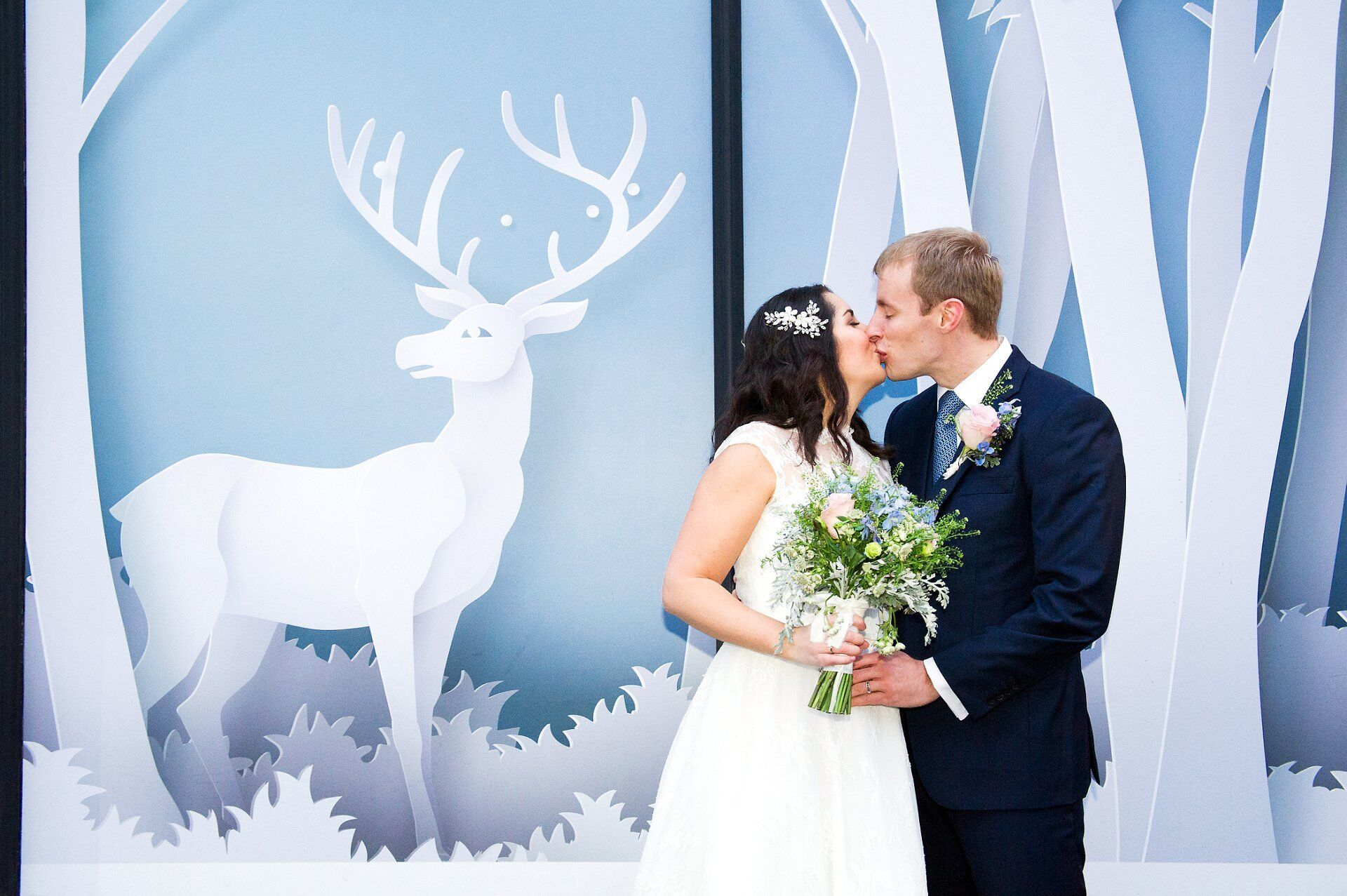 bluebird chelsea wedding photographer bride and groom kissing on london's king's road in front of stag winter scene