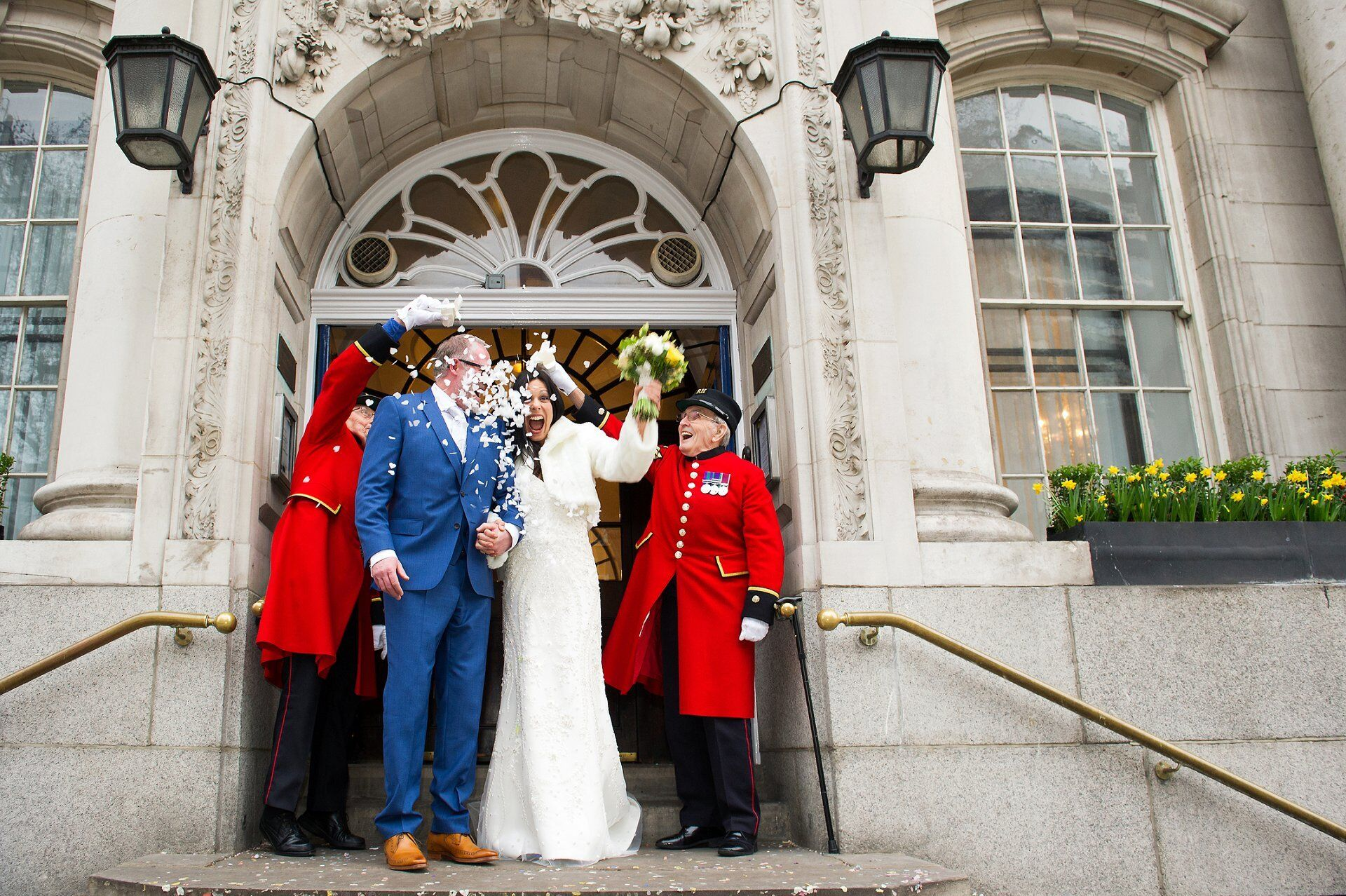 bride and groom leaving chelsea old town hall with confetti thrown by two chelsea pensioners