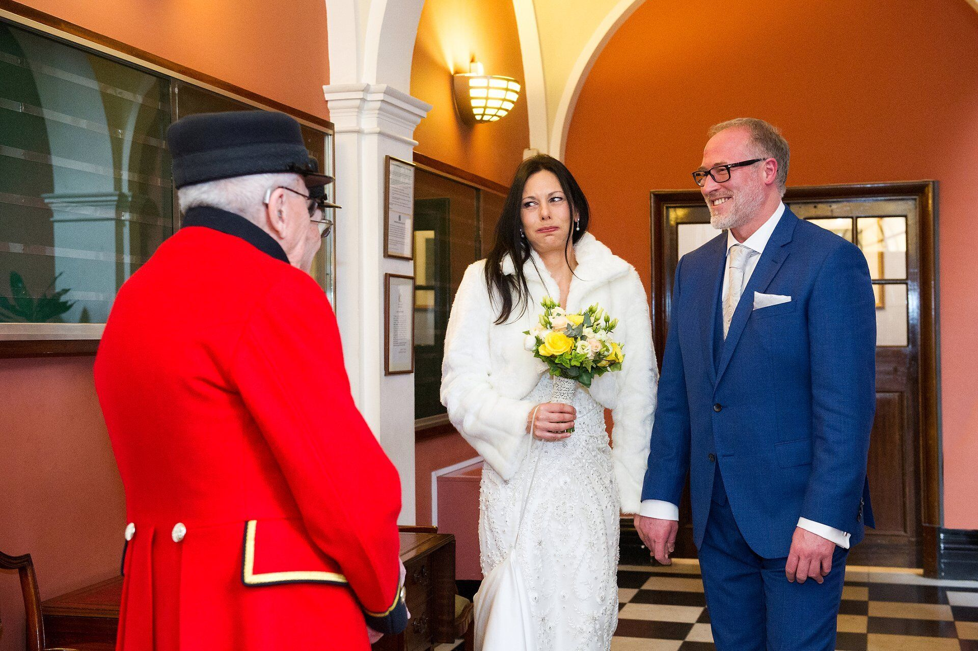 bride and groom meeting chelsea pensioners in waiting area for chelsea register office wedding