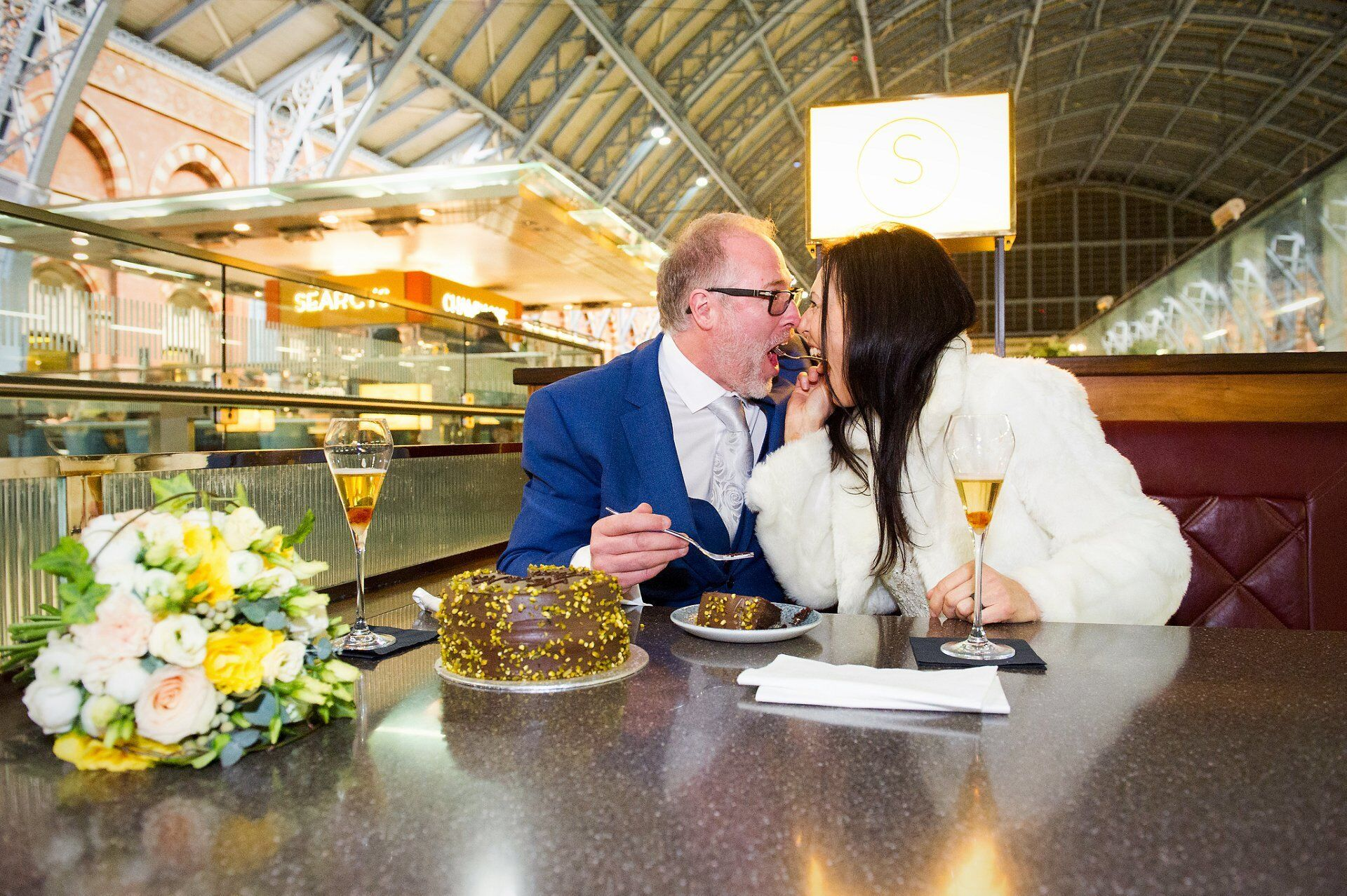 bride and groom share wedding cake in art deco styled grand terrace champagne bar at st pancras