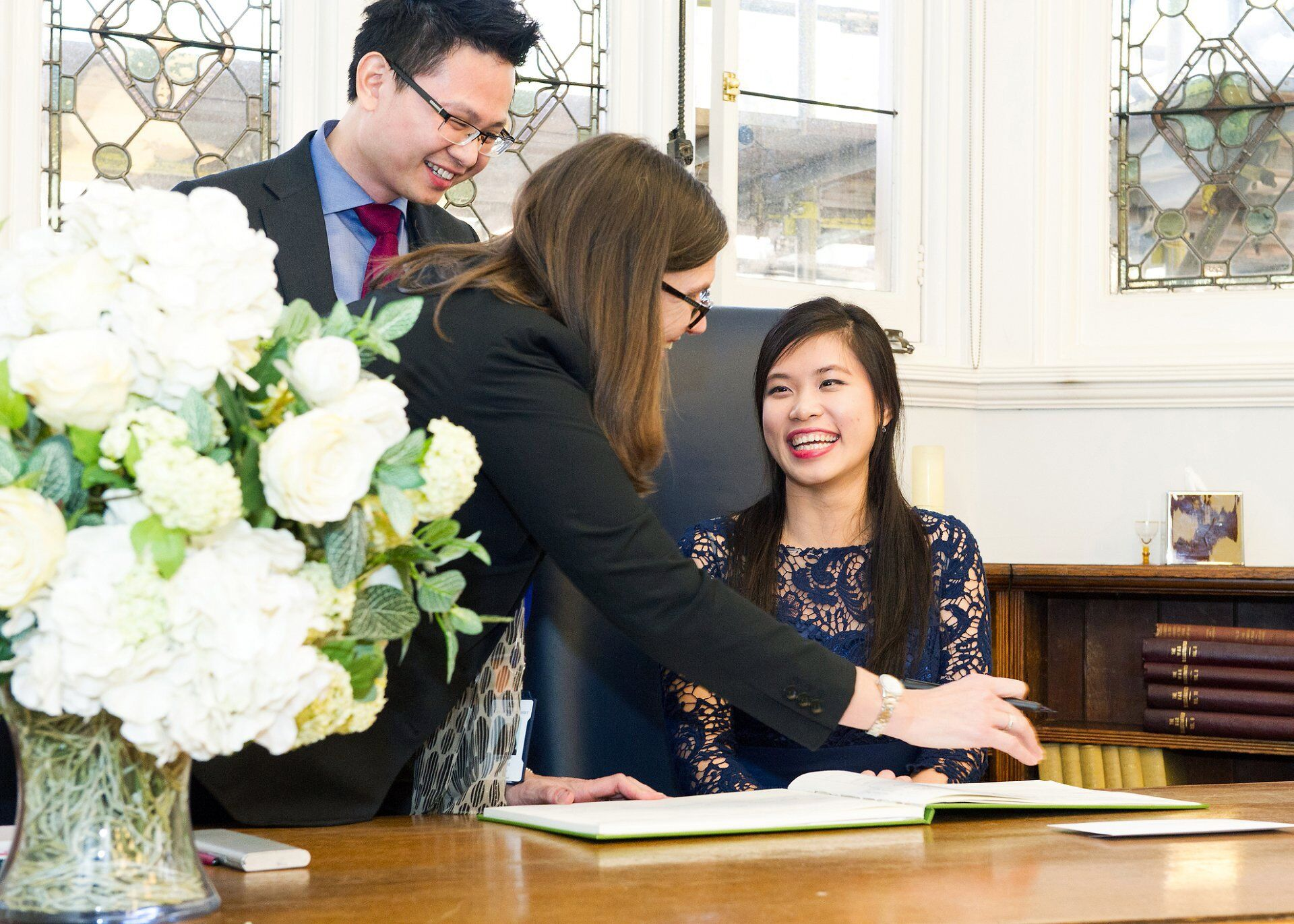 bride laughs with westminster registrar during signing by mayfair library wedding photographer