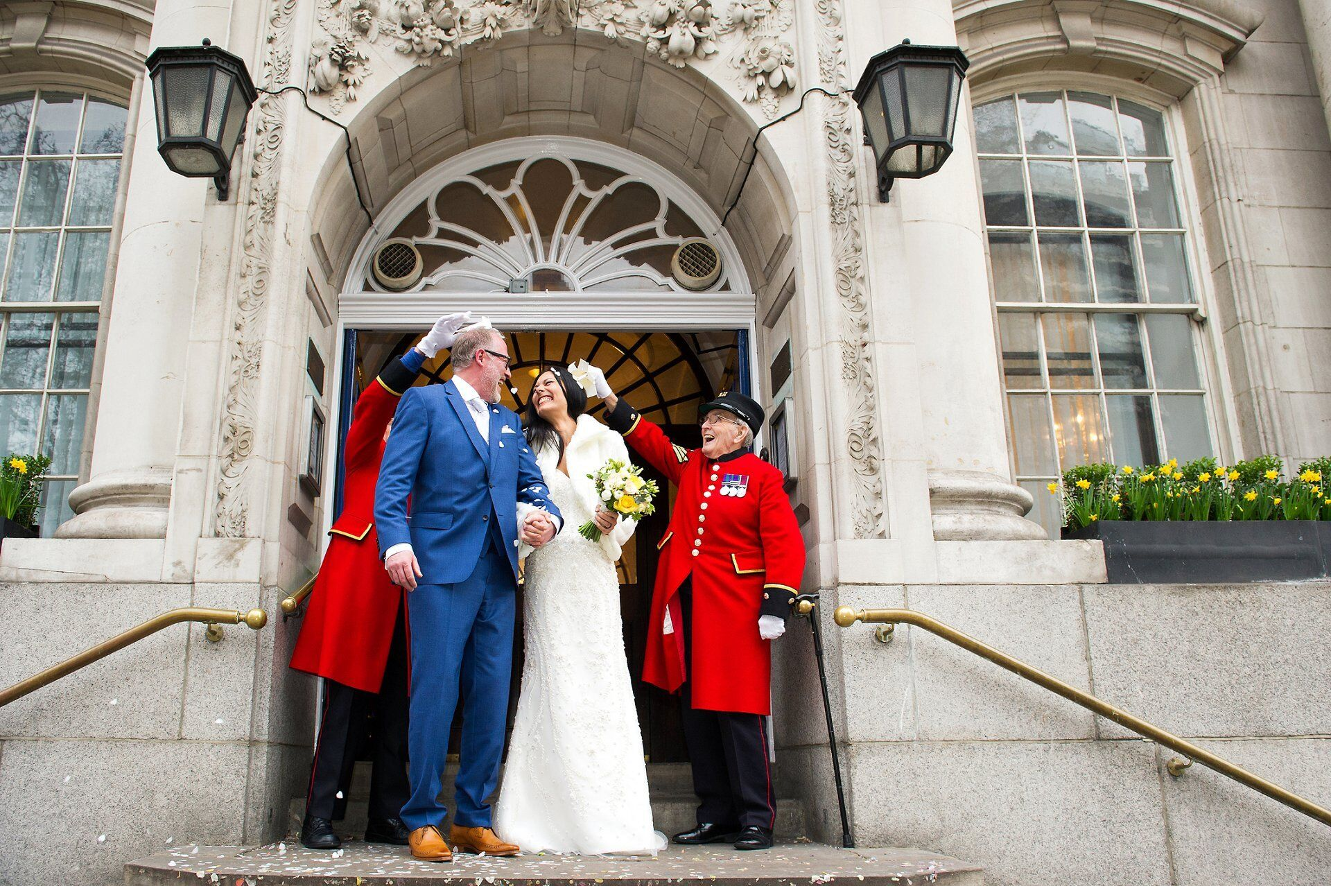 chelsea old town hall wedding photography outside on the famous steps with chelsea pensioners throwing confetti