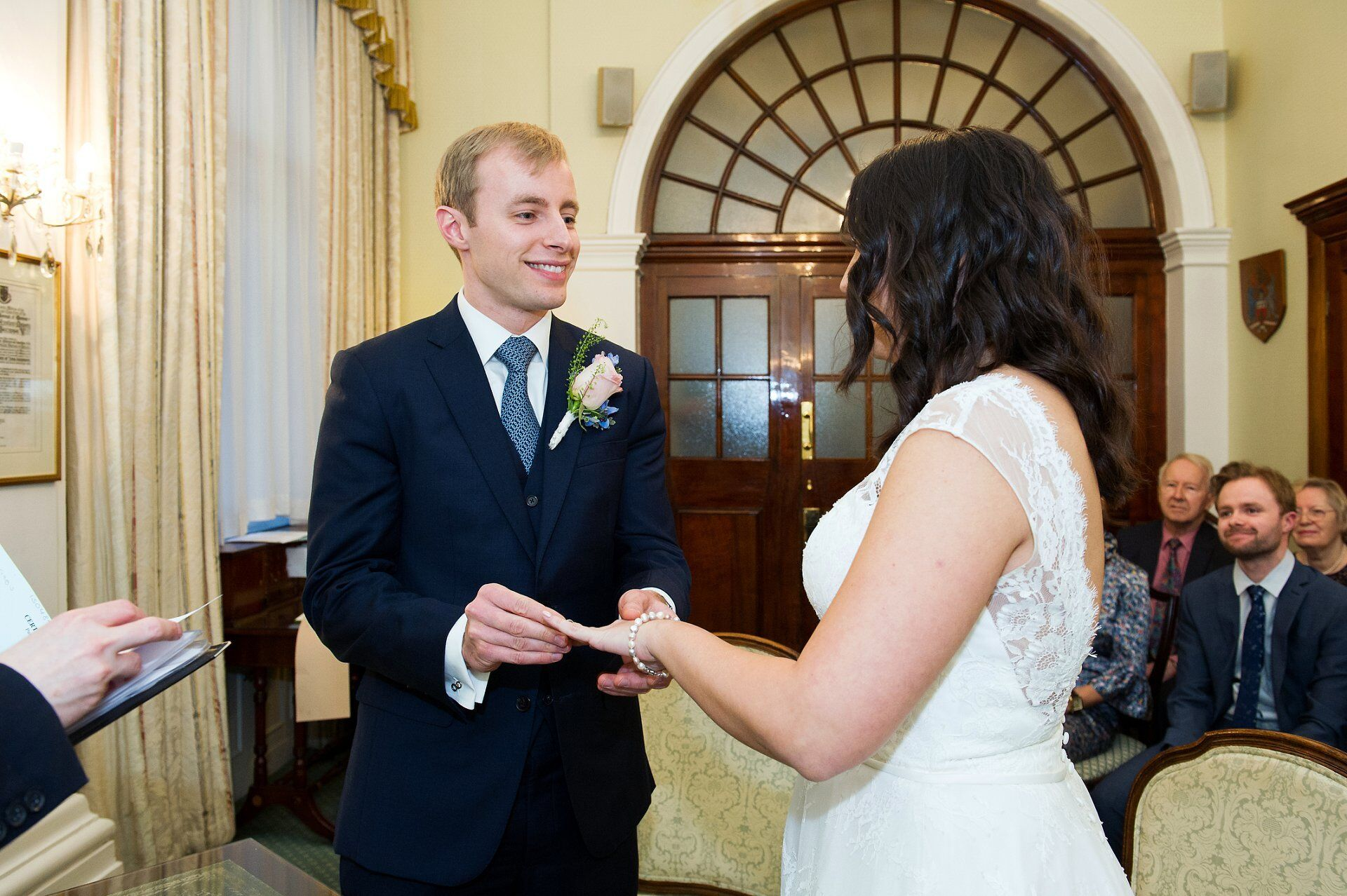 groom places ring on brides finger during rossetti room ceremony