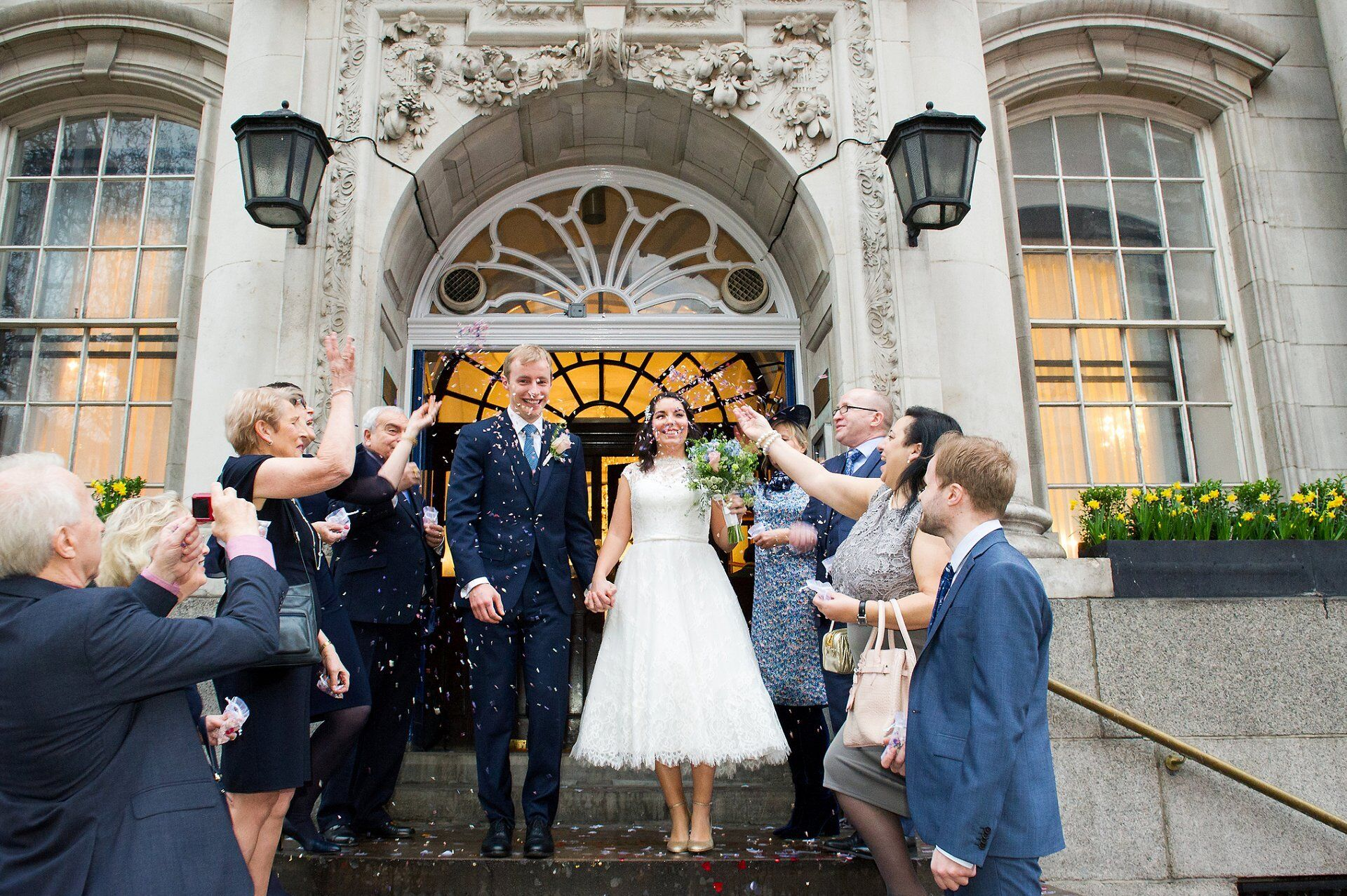 rainy confetti at chelsea old town hall wedding photographer bride wearing tea length wedding dress