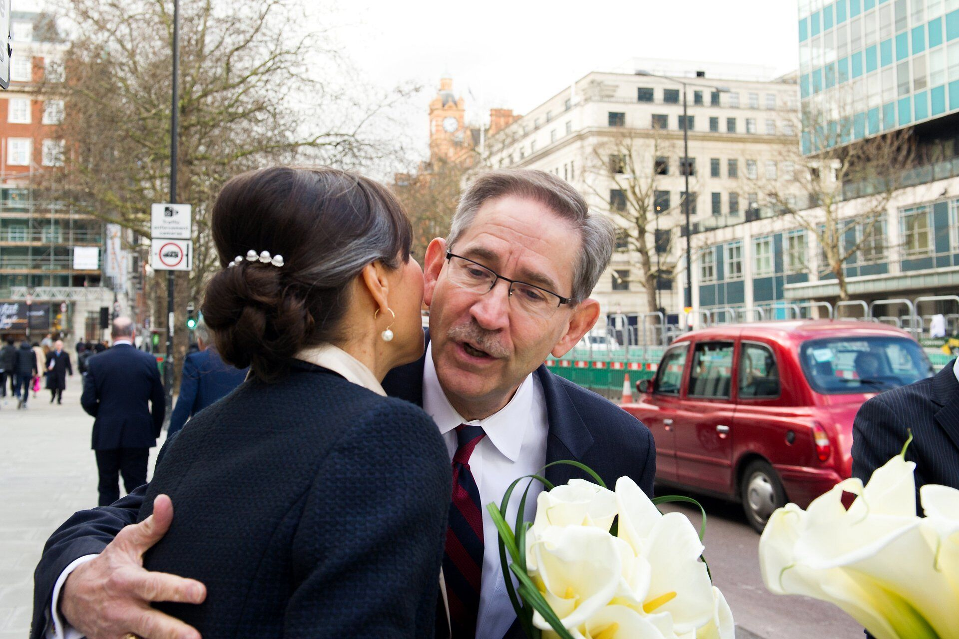 a guest greeting the bride outside old marylebone town hall