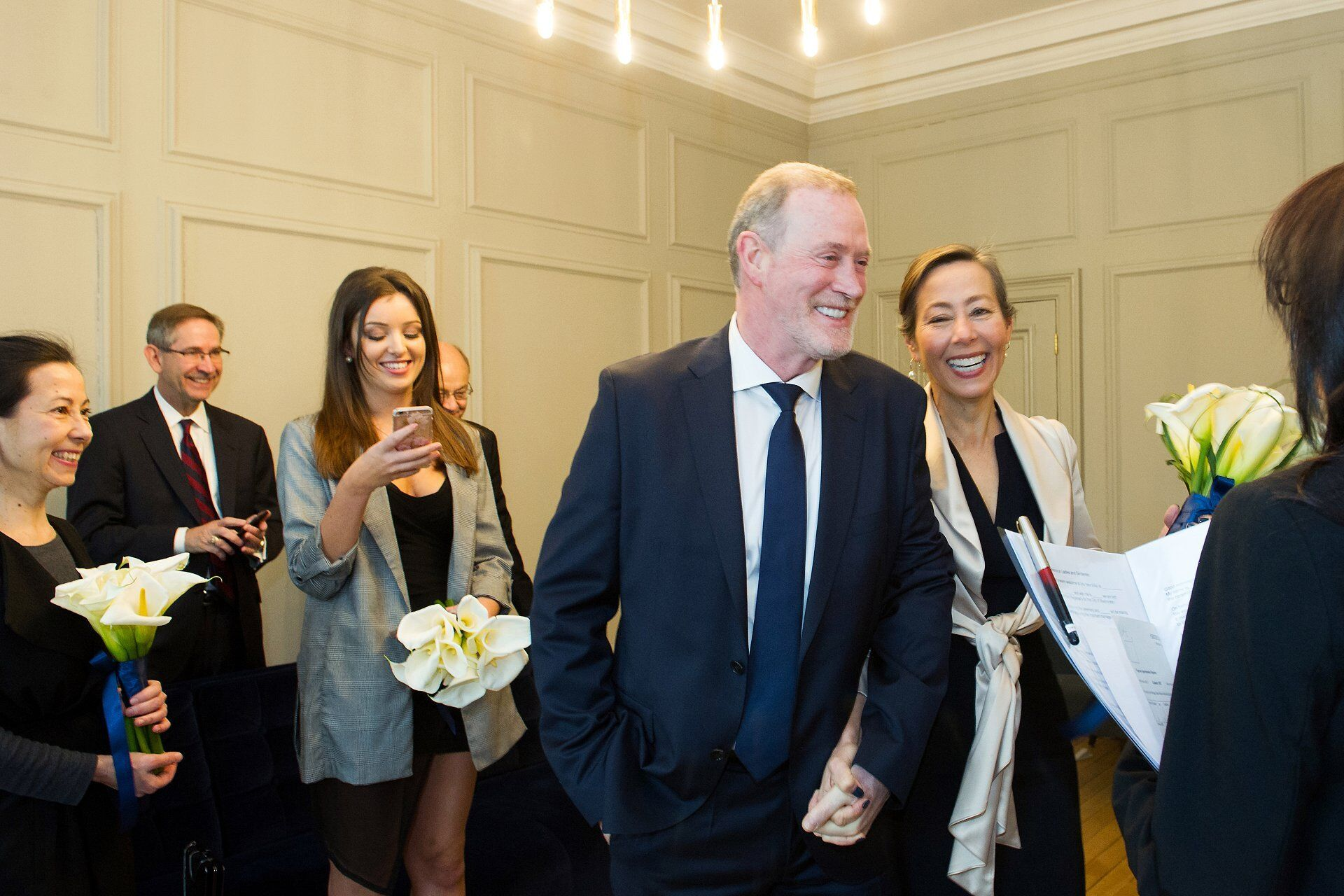 bride and groom enter soho room wedding ceremony at old marylebone town hall full of smiles