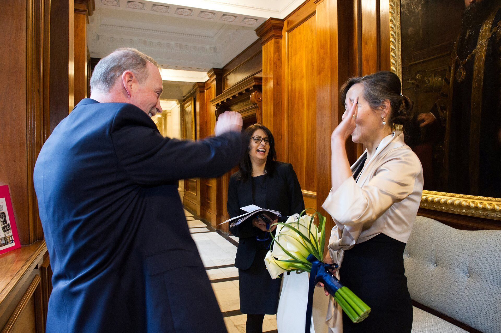 bride and groom high five after their old marylebone town hall wedding captured by emma duggan the best register office wedding photographer in london