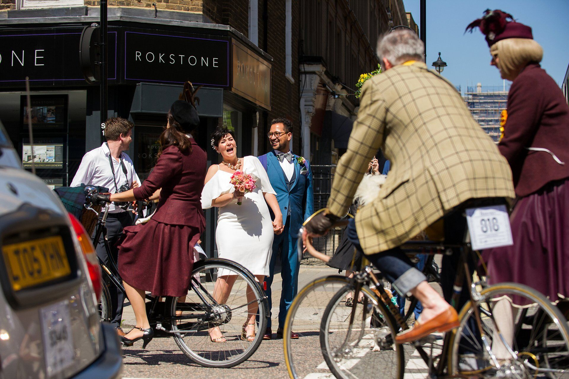 annual tweed bicycle ride on london's chiltern street with just married couple looking on and laughing (after their marylebone room ceremony)