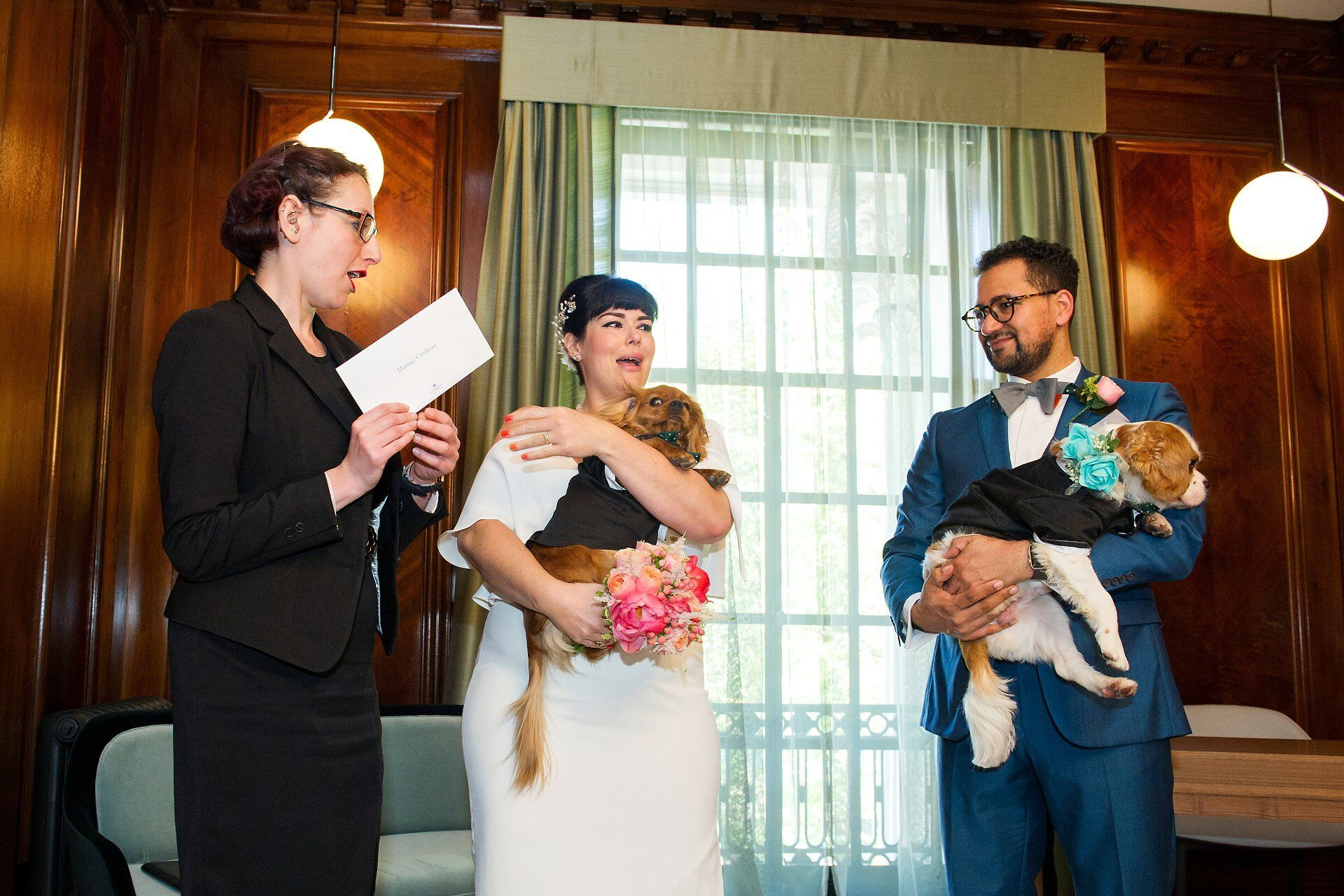 westminster register office registrar hands marriage certificate to the bride and groom, each holding a cavalier king charles spaniel puppy dog (dog friendly wedding venue)