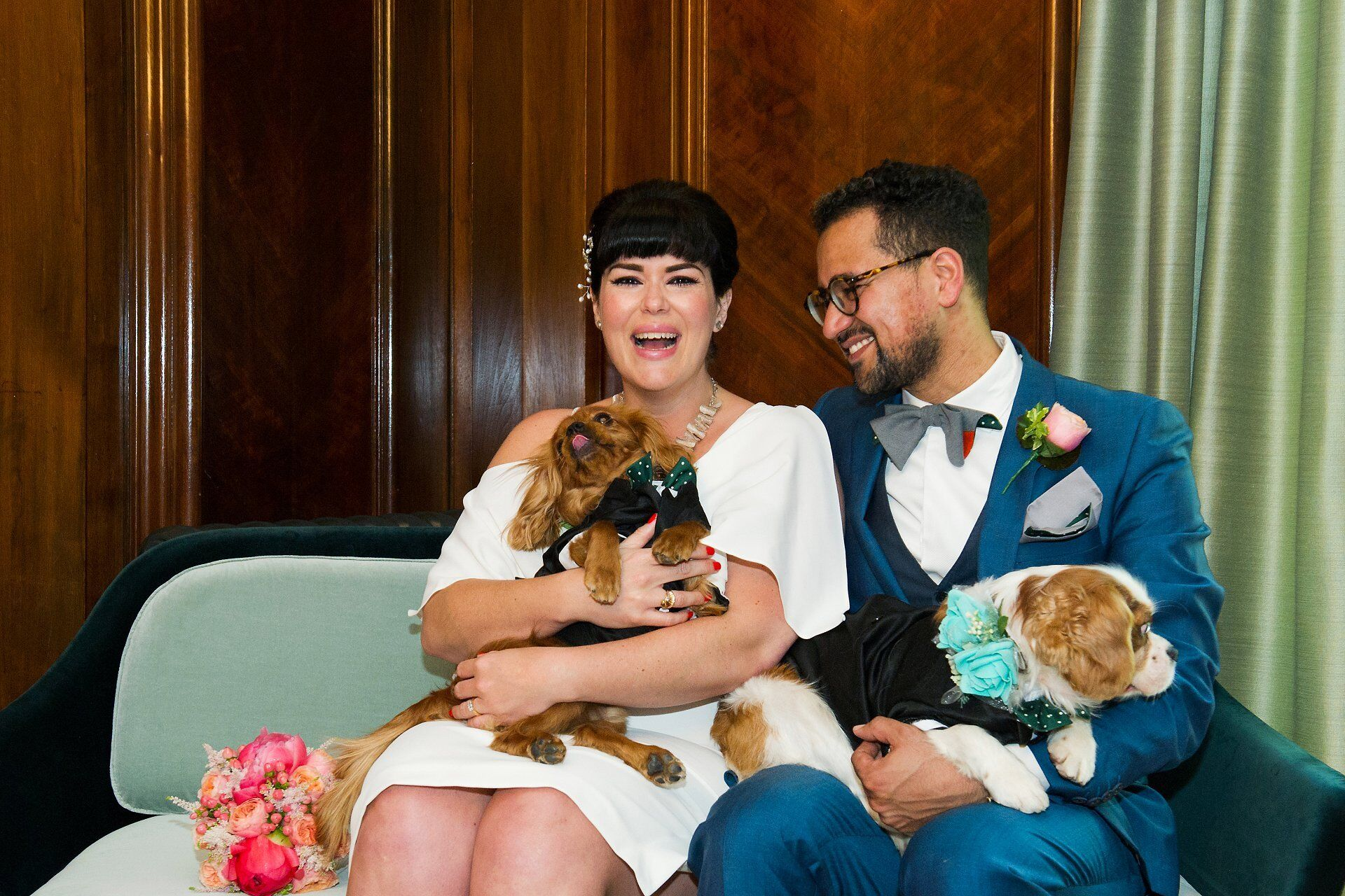 bride and groom with their two puppy dogs after their marylebone room wedding at old marylebone town hall