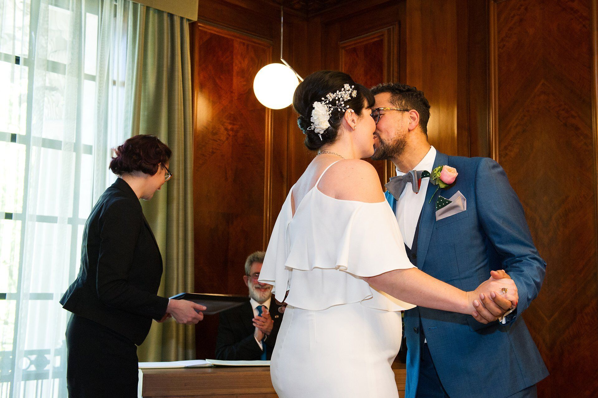 bride and groom kiss to celebrate their marriage in the refurbished wood panelled marylebone room at old marylebone town hall