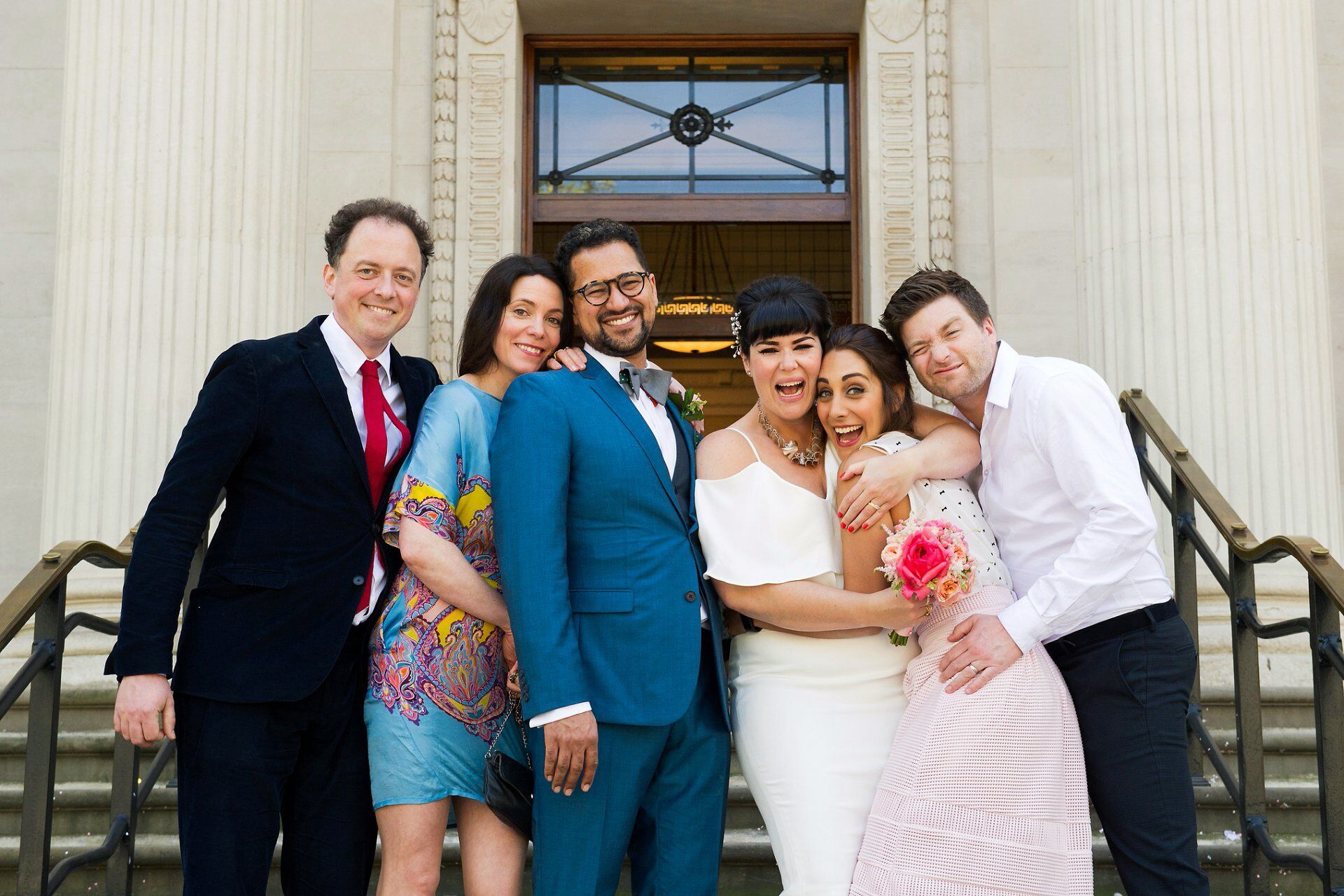 bride and groom and friends on the steps outside old marylebone town hall after their marylebone room ceremony