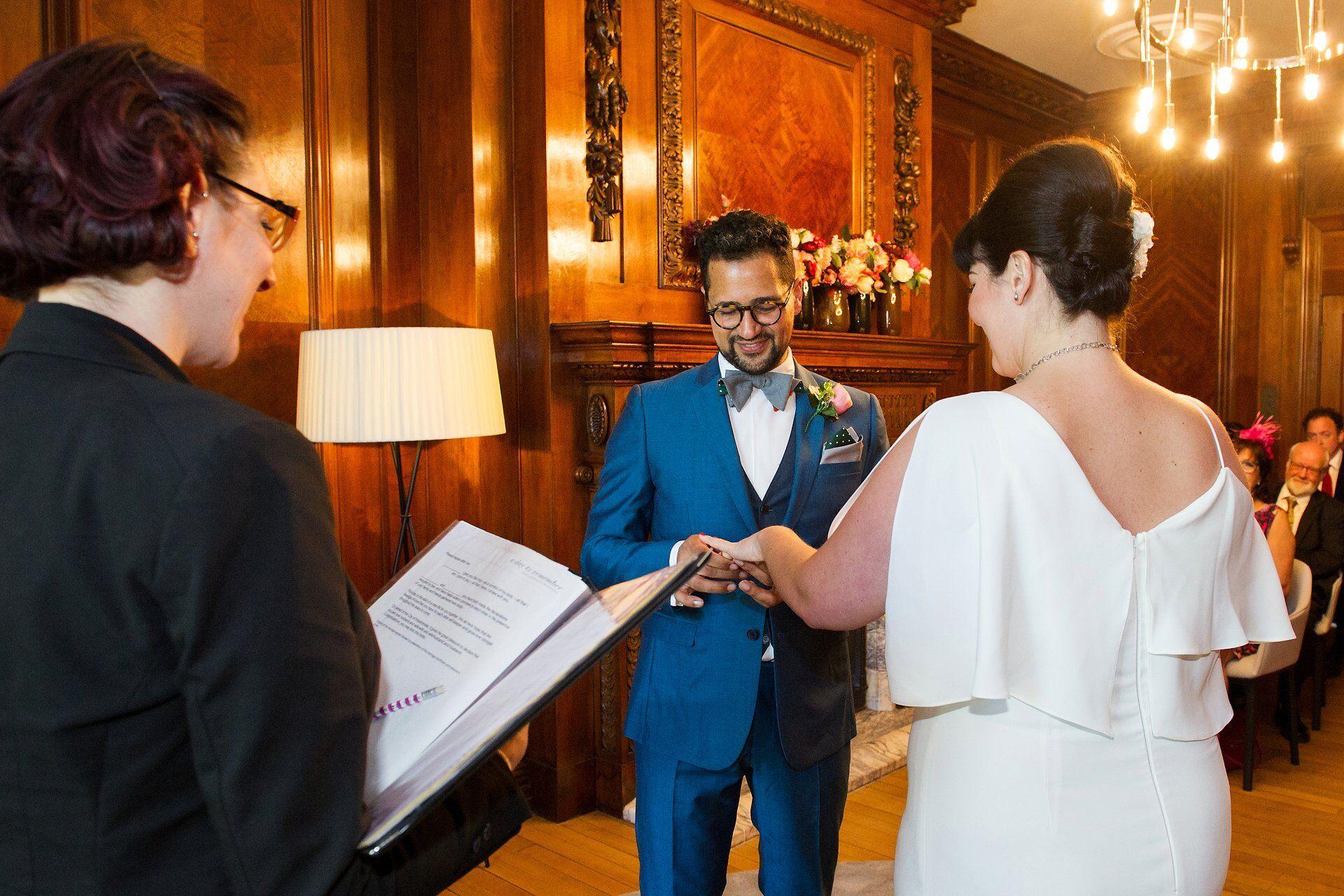 marylebone room civil wedding ceremony ring exchange with groom in vintage Donna Karan suit