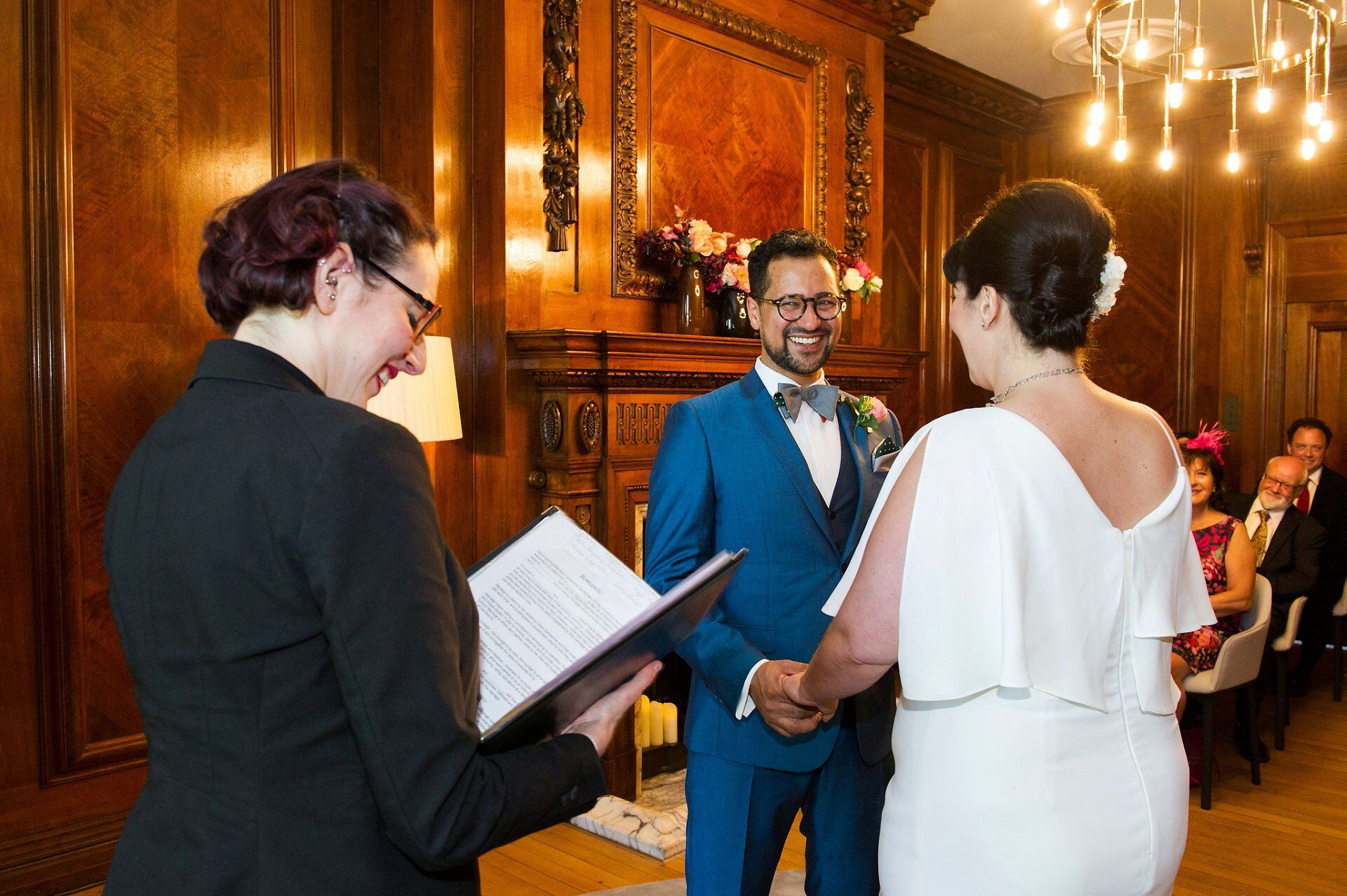 vintage groom laughing during his civil wedding ceremony in the marylebone room by recommended old marylebone town hall wedding photographer emma duggan