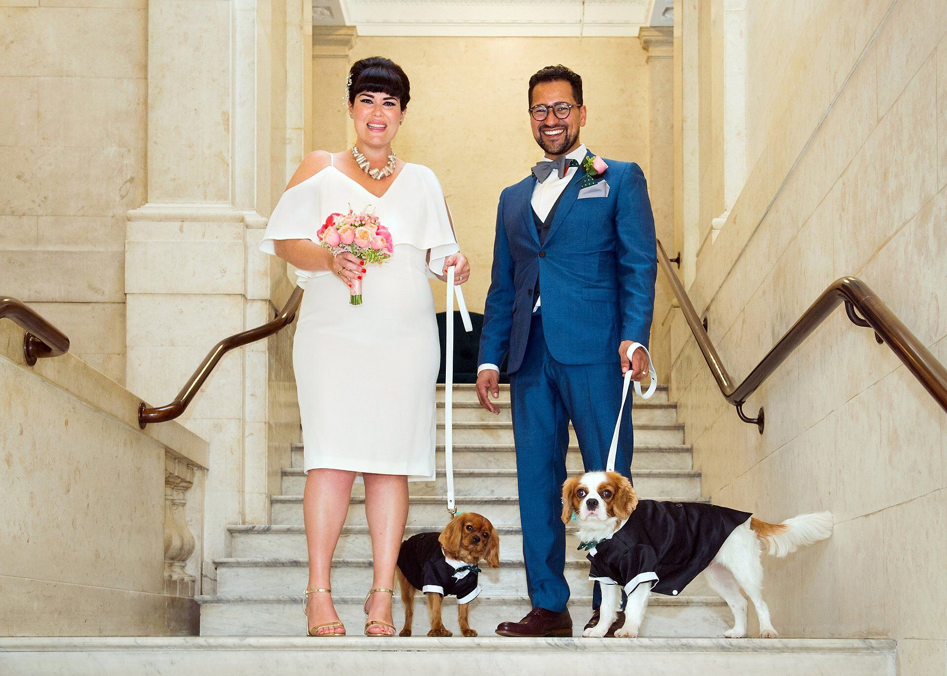pet friendly wedding venue london (westminster register office) - old marylebone town hall here a bride and groom and their two puppies pose on the marble staircase