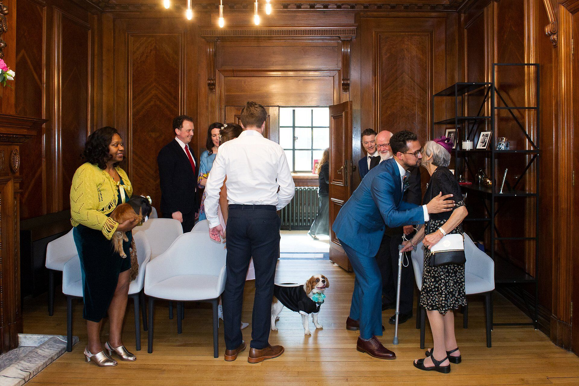 marylebone room wedding photography with dogs as ring bearers here the groom greets his guests as the dogs look on
