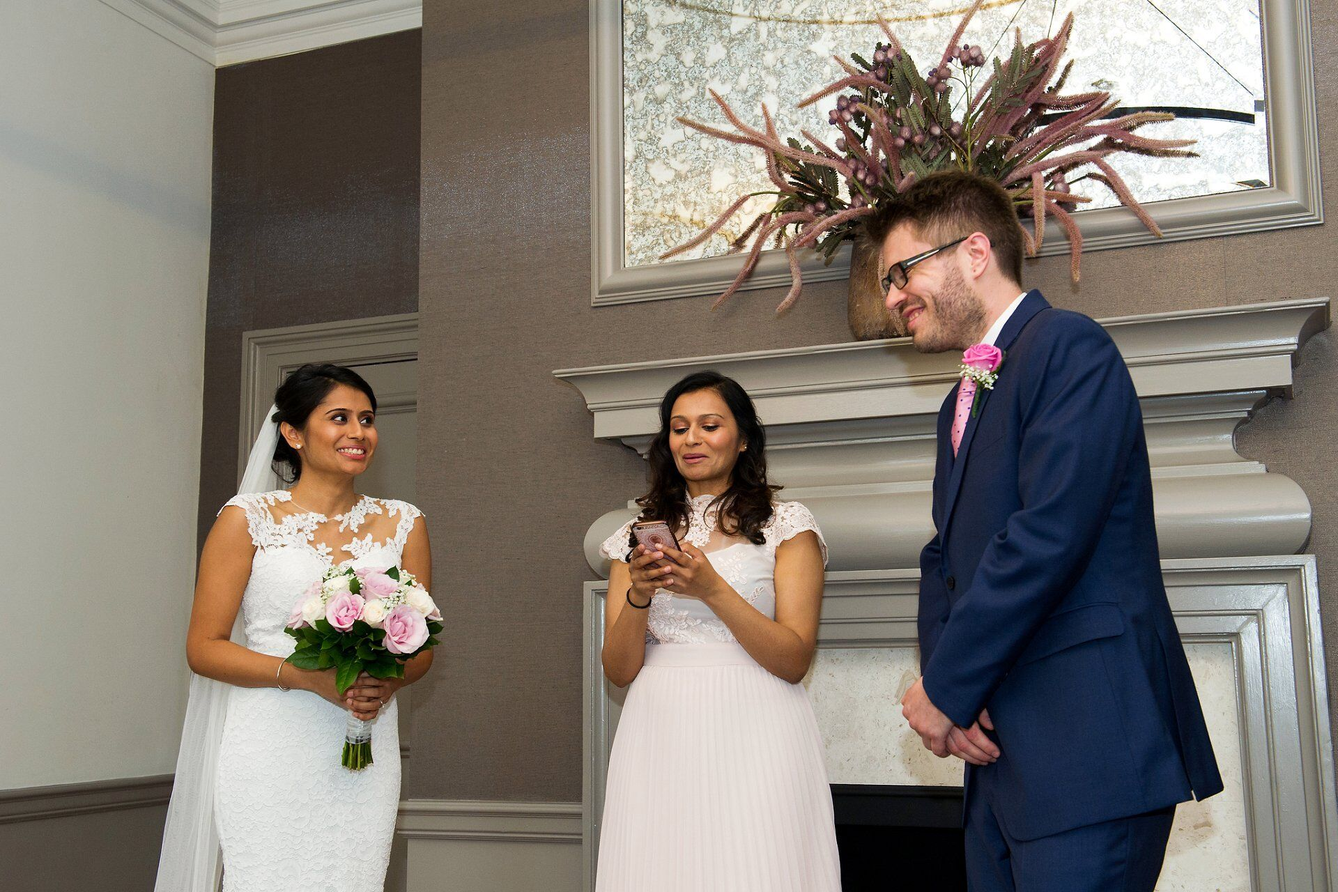 bride and groom smiling during sister's reading in small anglo indian wedding ceremony london