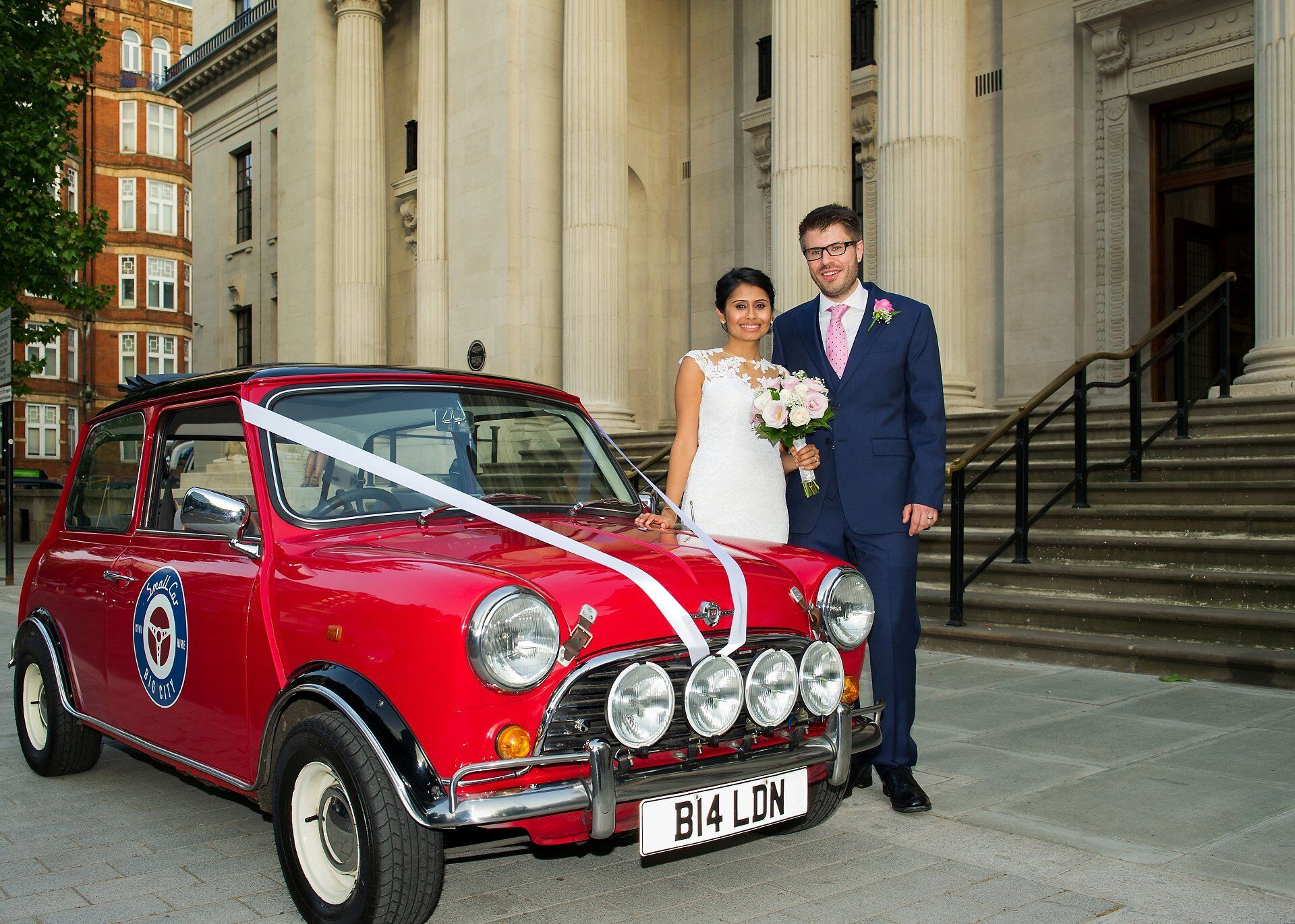 couple pose with small car big city vintage mini outside old marylebone town hall
