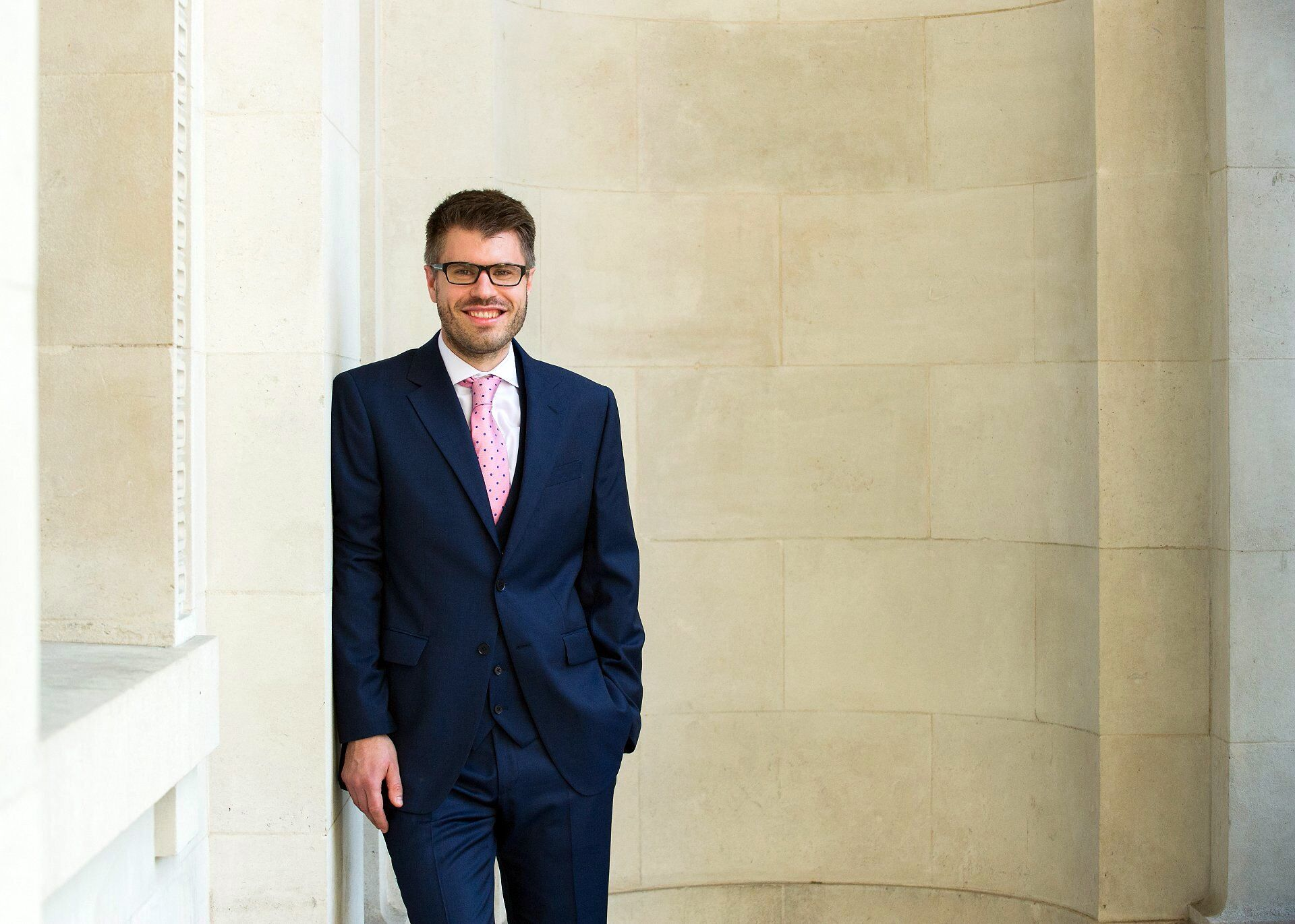 groom in navy suit pink spotty tie by old marylebone town hall wedding photographer emma duggan
