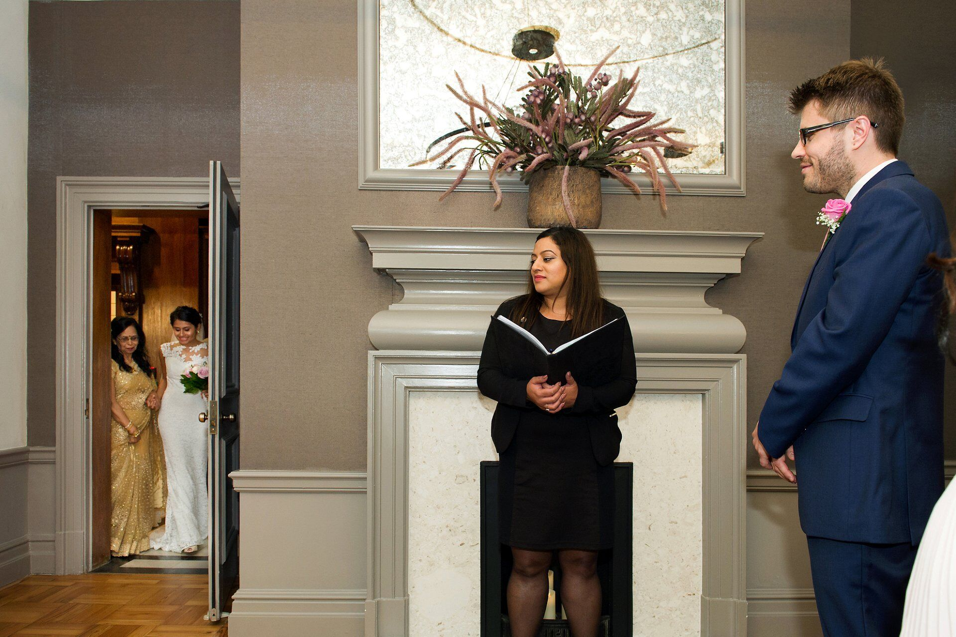 indian bride and mother enter mayfair room with groom watching by mayfair room wedding photographer emma duggan