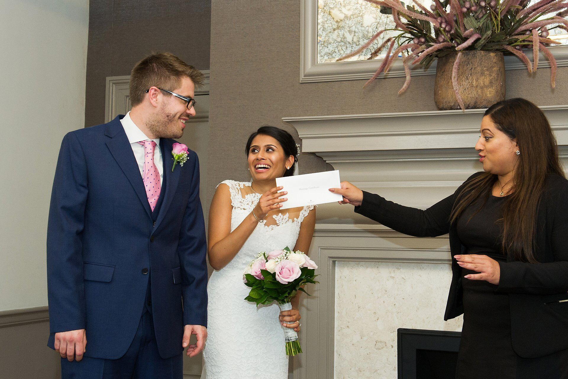 registrar hands marriage certificate to bride old marylebone town hall wedding photographer