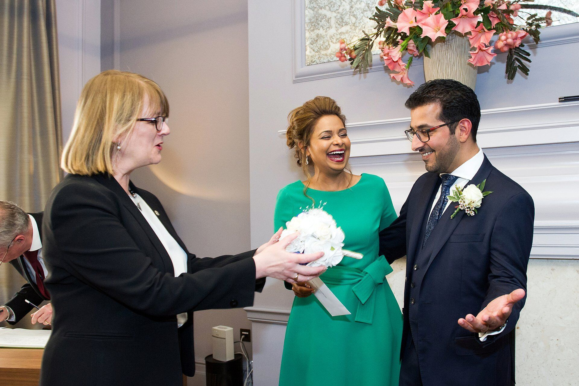 alison cathcart superintendent registrar westminster register offiice hands groom brides bouquet in knightsbridge room