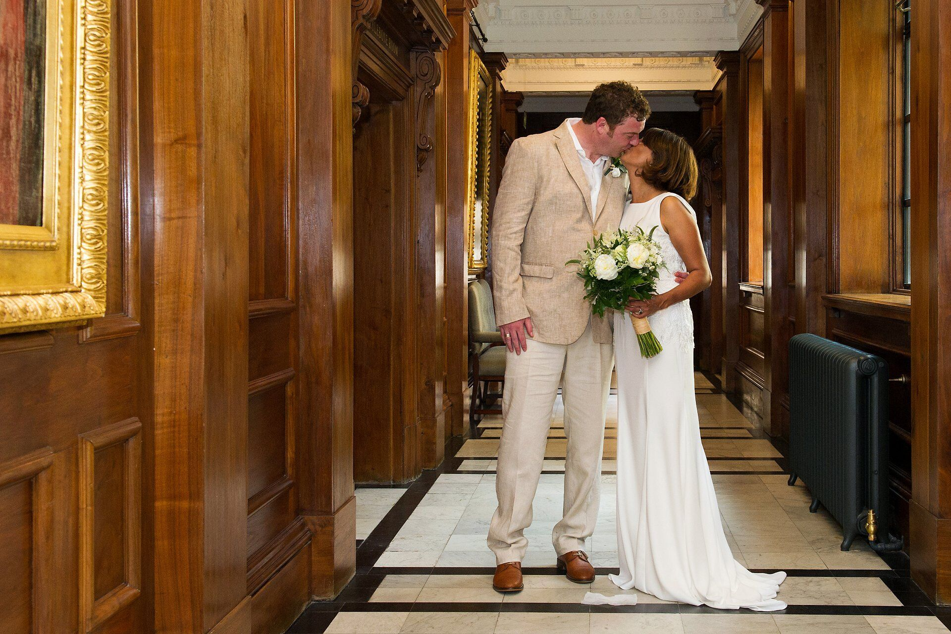 bride and groom kissing on the first floor corridor at old marylebone town hall after their world cup quarter final wedding