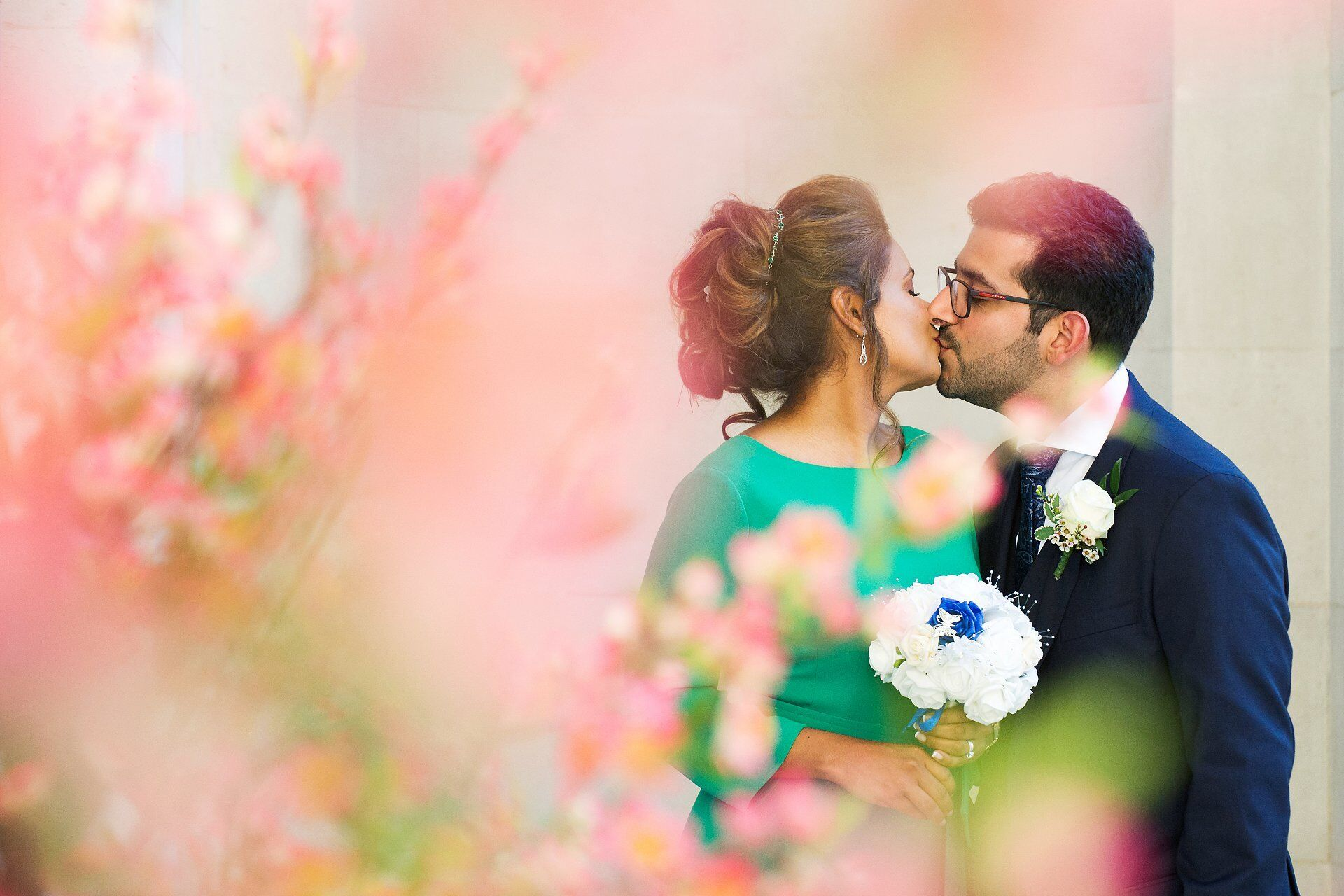 bride and groom kissing with spring flowers old maryleobne town hall wedding photography by a short coverage package specialist