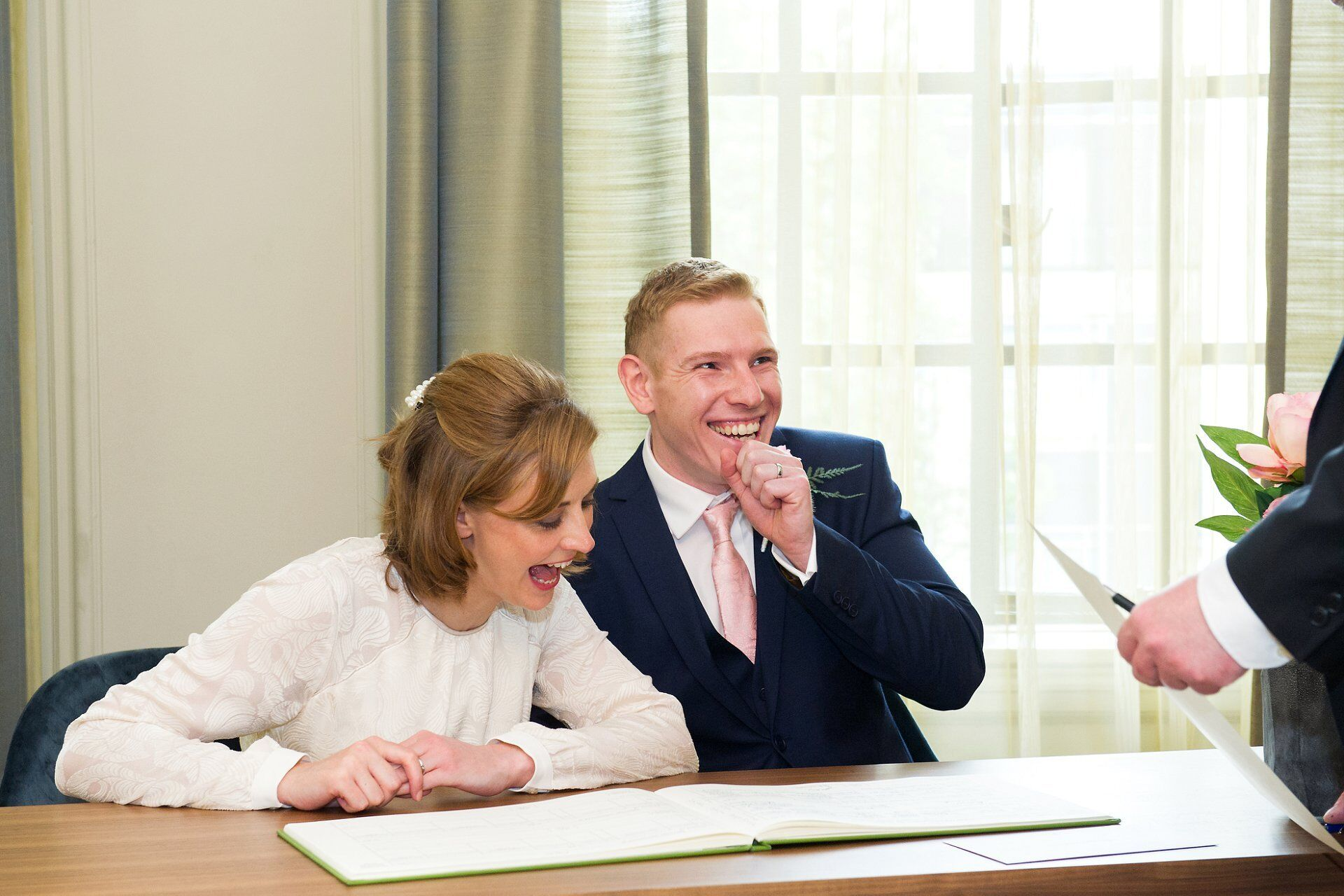 bride and groom laughing during signing of the register at westminster register office
