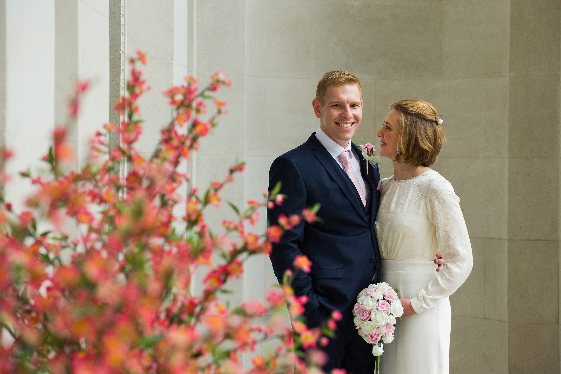 bride and groom pose for portrait by old marylebone town hall wedding photographer emma duggan