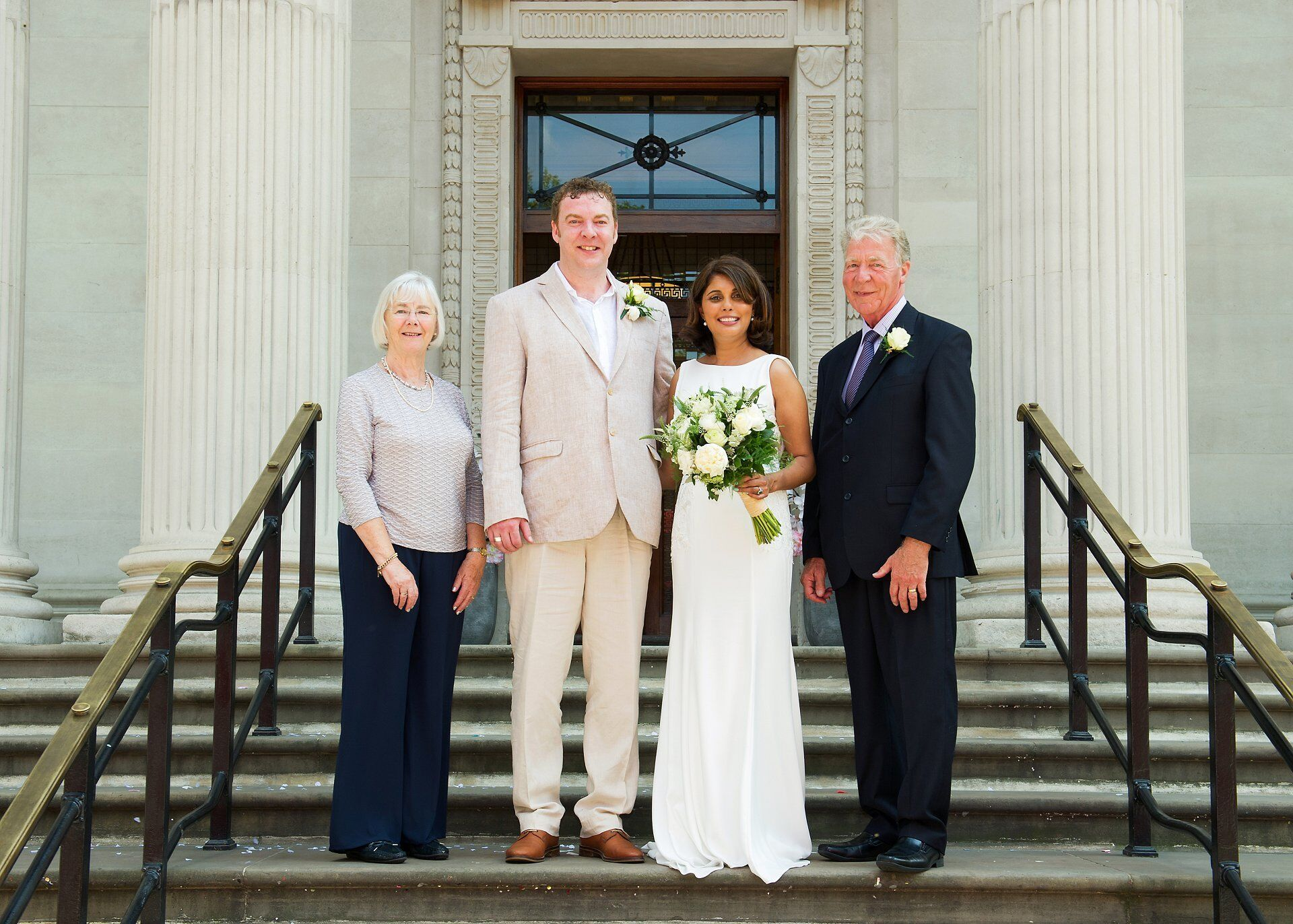 bride and groom with parents on the steps outside westminster register office by specialist old marylebone town hall wedding photographer