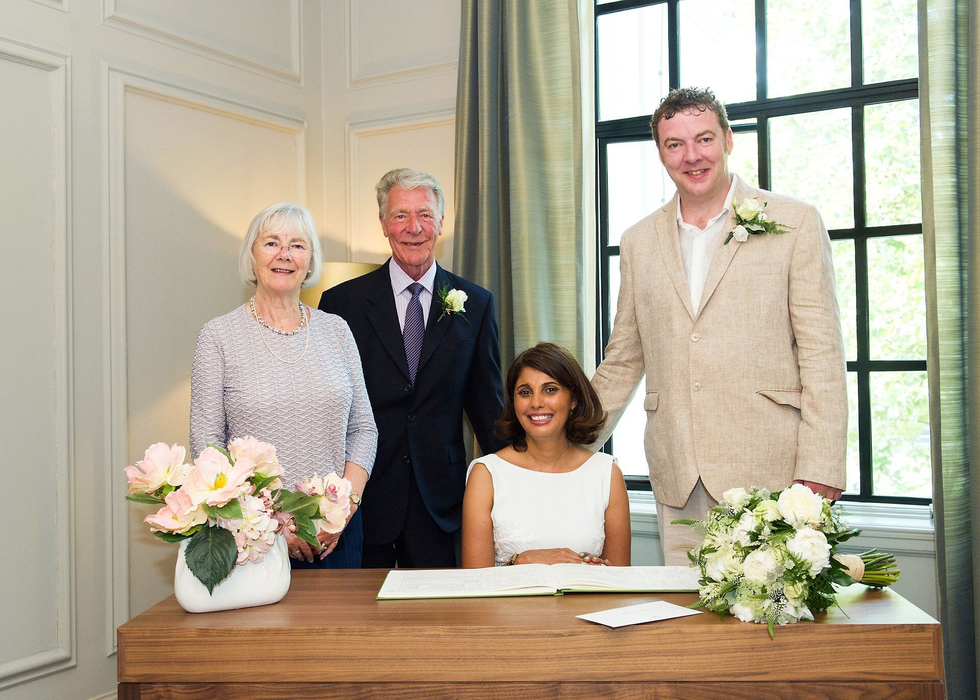 bride groom and his parents pose for a photo after this soho room civil wedding ceremony