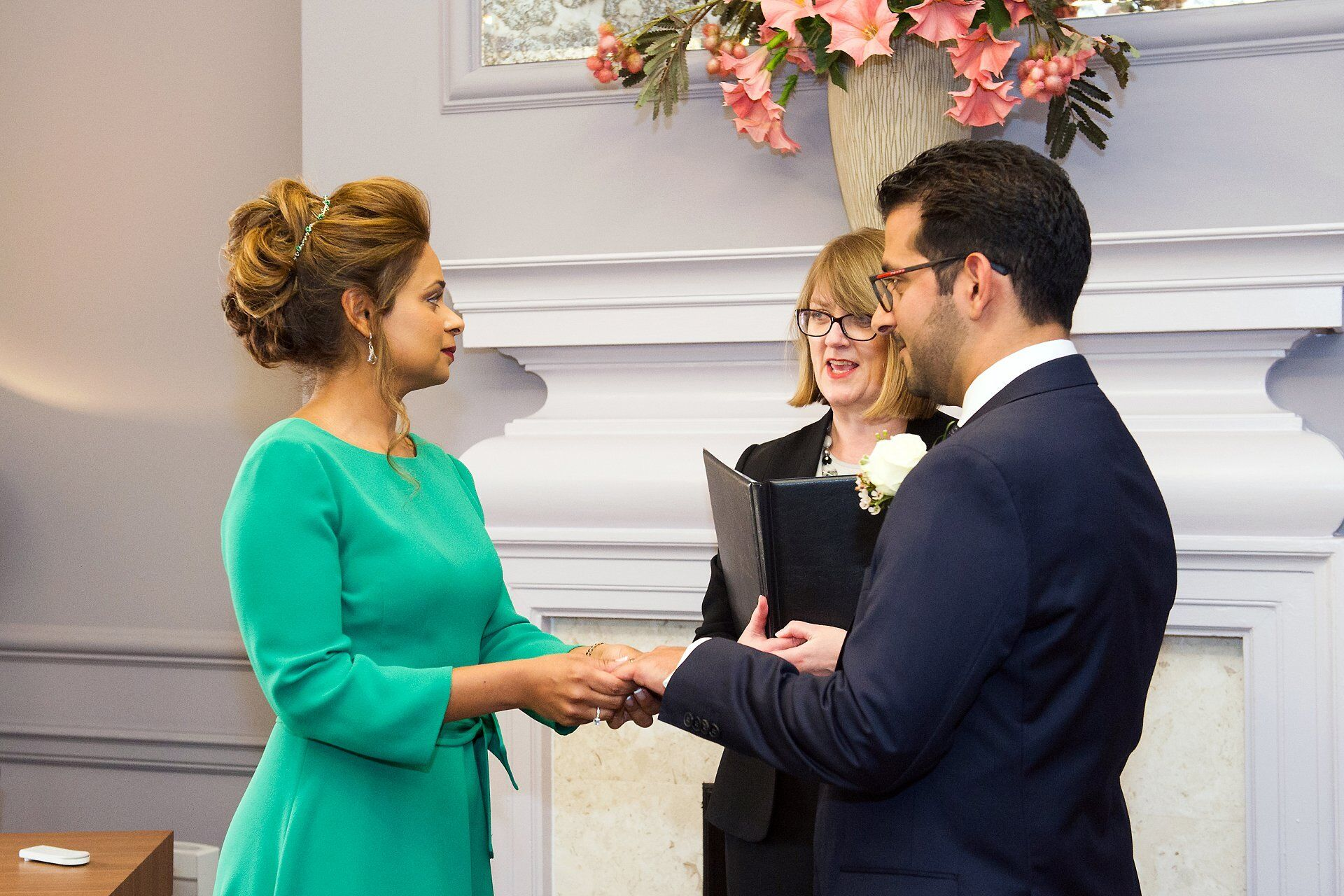 bride places ring on her partners finger westminster register office wedding photography in the knightsbridge room