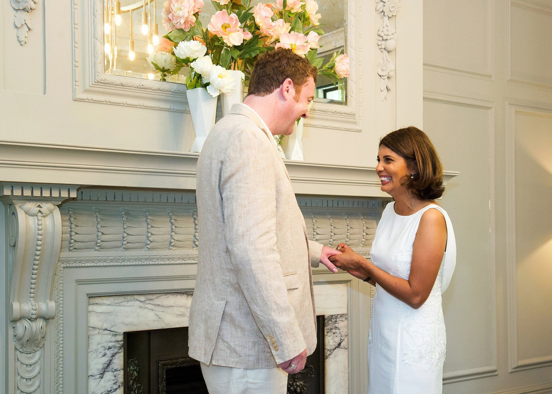 bride smiling as she places thh ring on her husband's finger during old marylebone town hall wedding