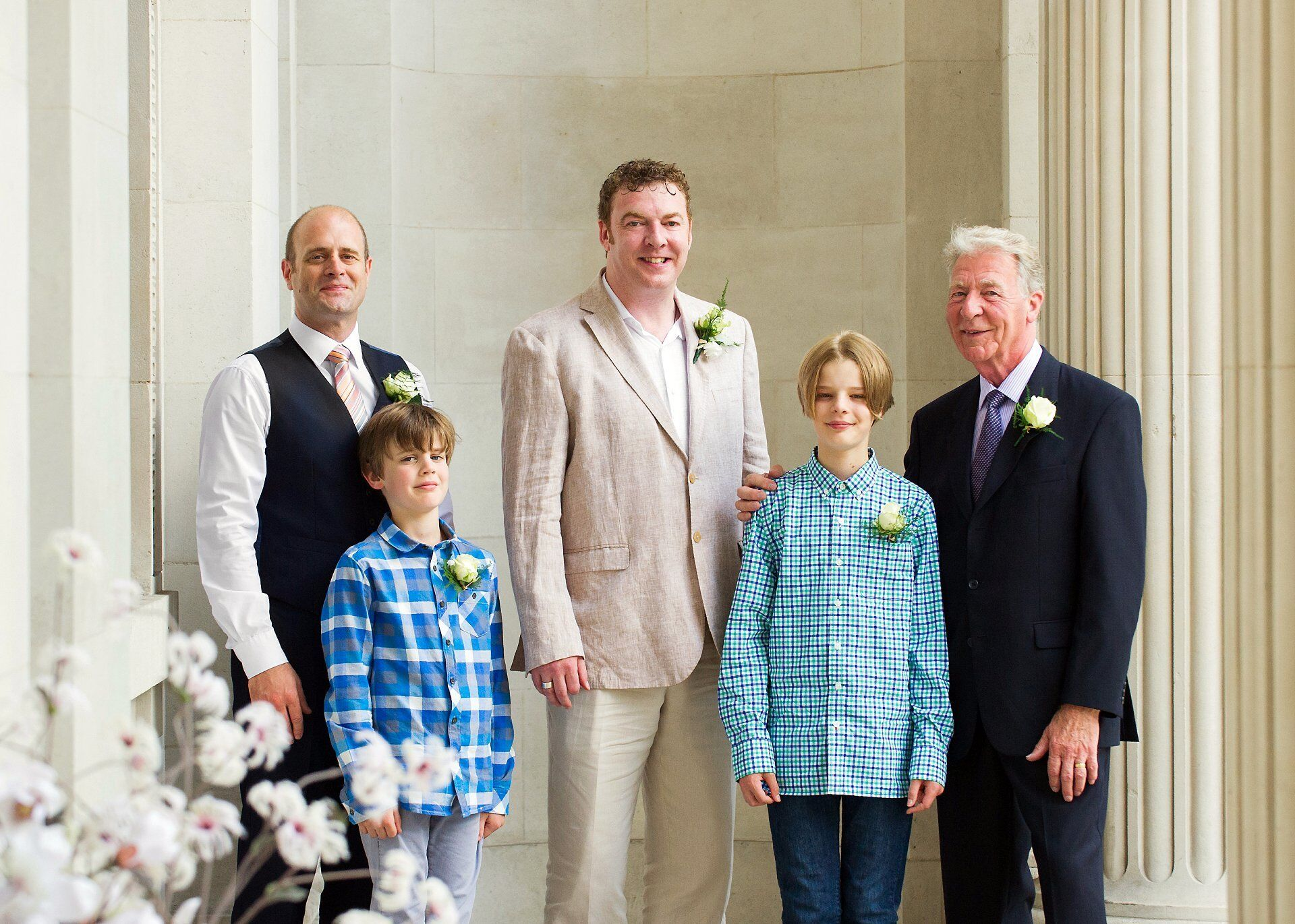 groom and fmaily in group photograph just before his summer world cup quarter final wedding in the soho room at old marylebone town hall