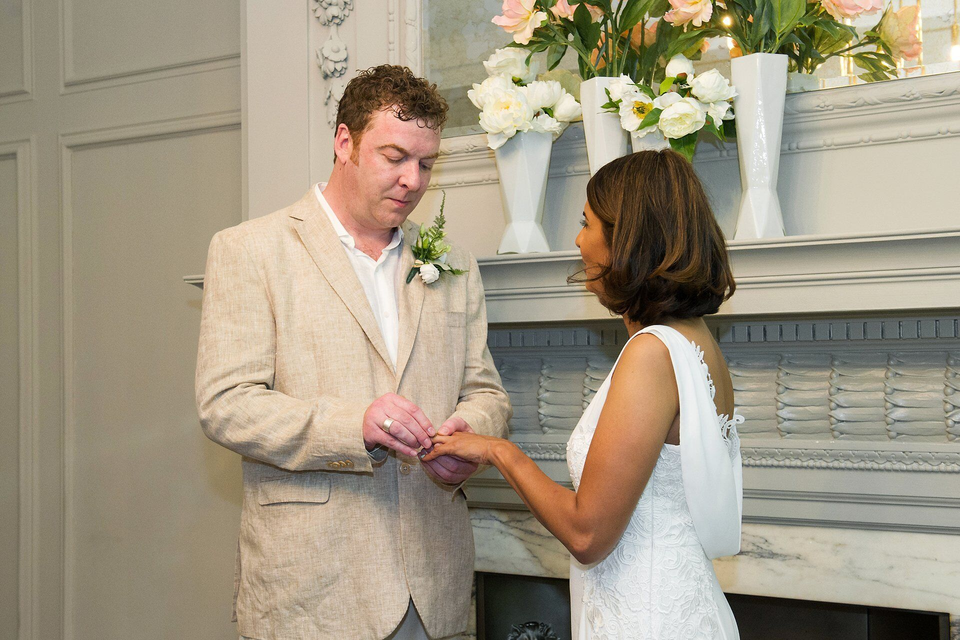 groom placing ring on his bride's finger during soho room wedidng ceremony photogrpahed by emma duggan