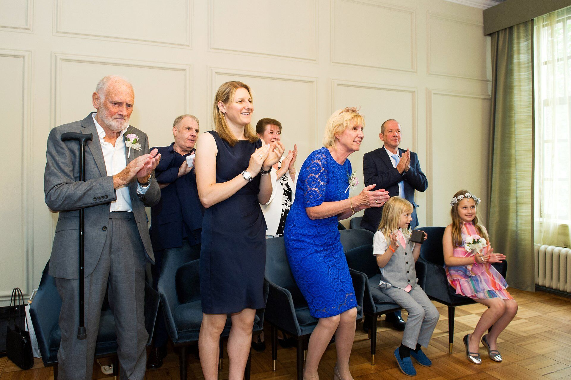 guests in the pimlico room at old marylebone town hall applaud the bride and groom