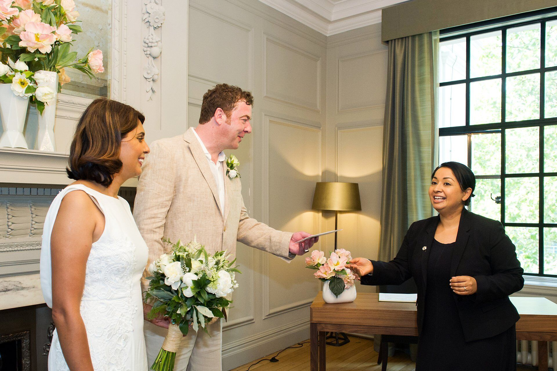 registrar from westminster council hands over the marriage certificate to a bride and groom in the soho room