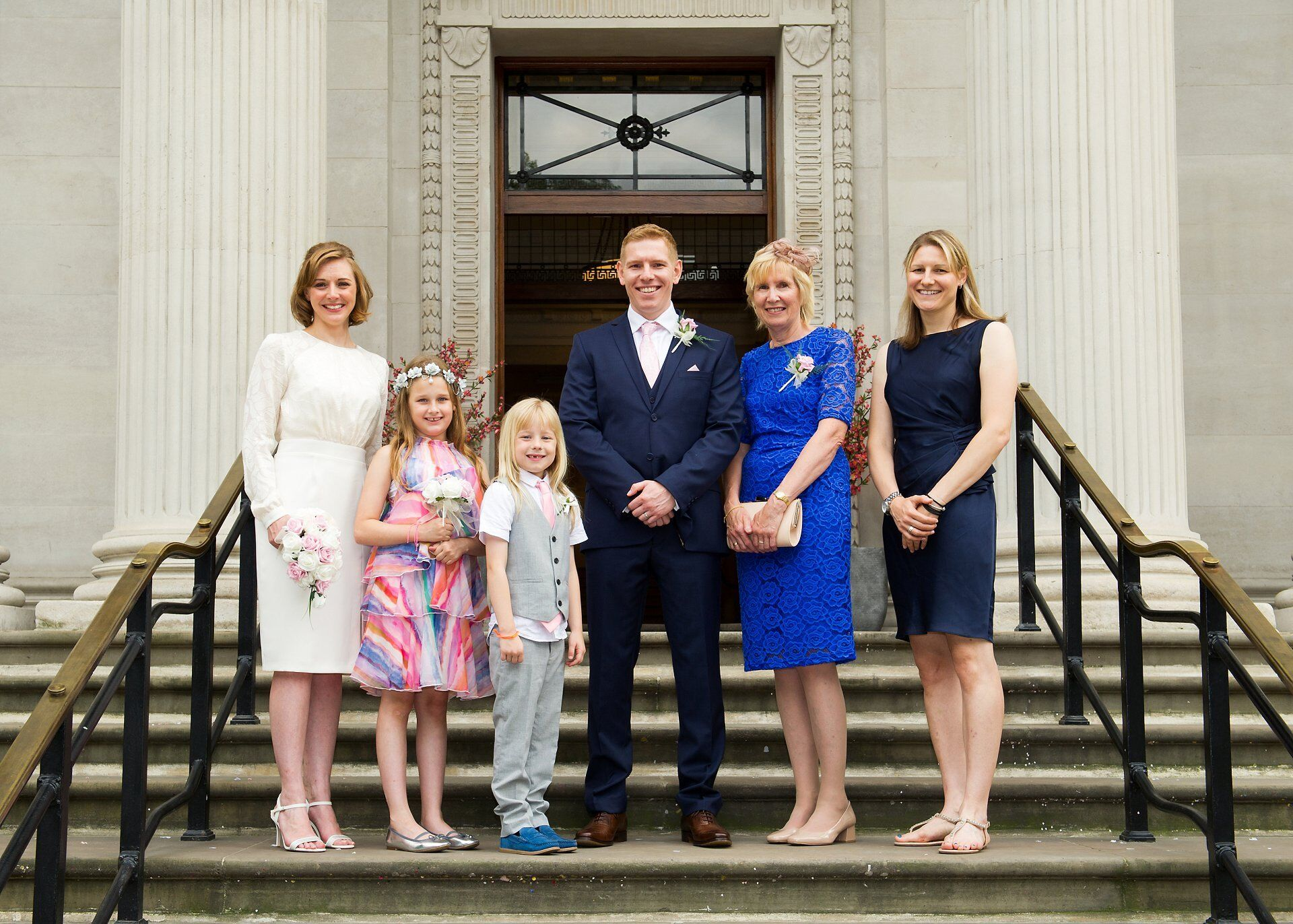 sping wedding in a london register office couple pose with family on steps