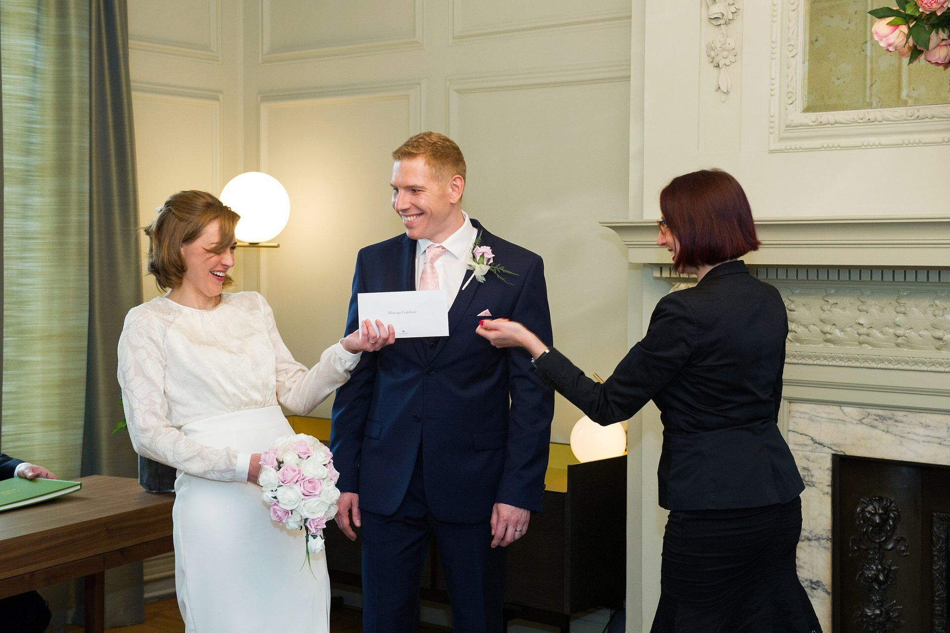 deputy superintendent registrar at westminster register office wedding hands over the marriage certificate to the laughing bride