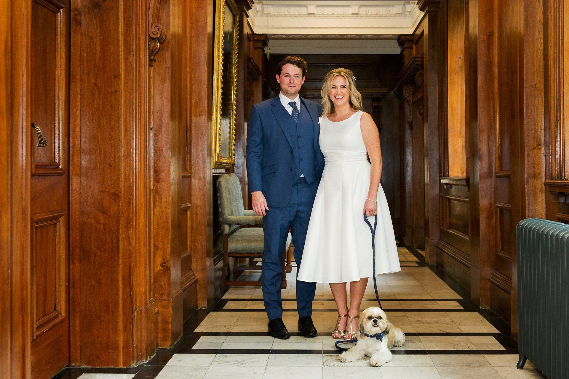 bride and groom outside the spho room with their fluffy dog jasper