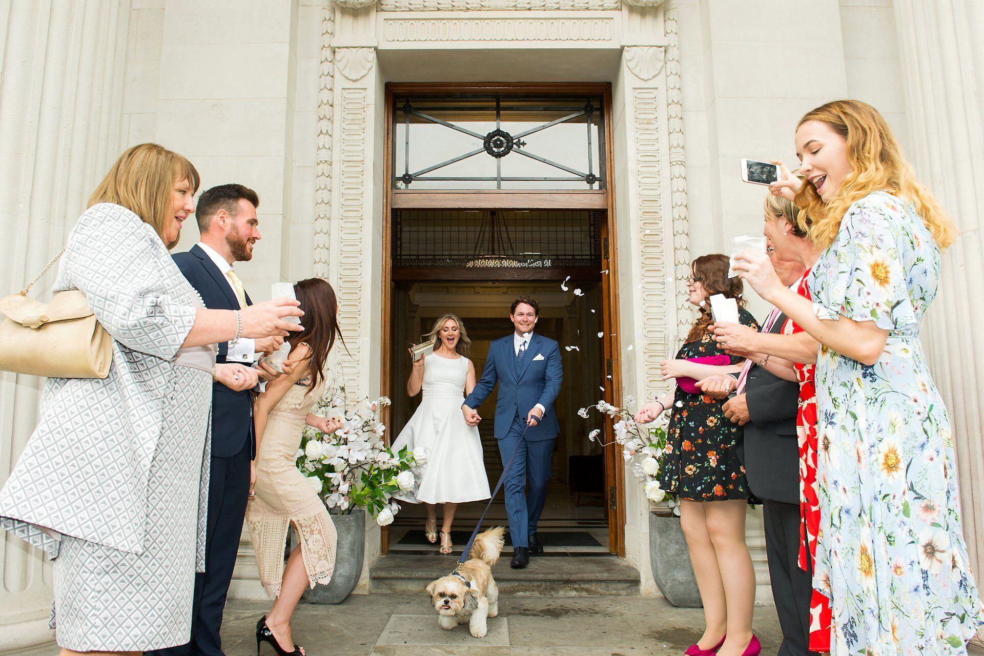 couple leaving old marylebone town hall as husband and wife with their little shih tzu dog