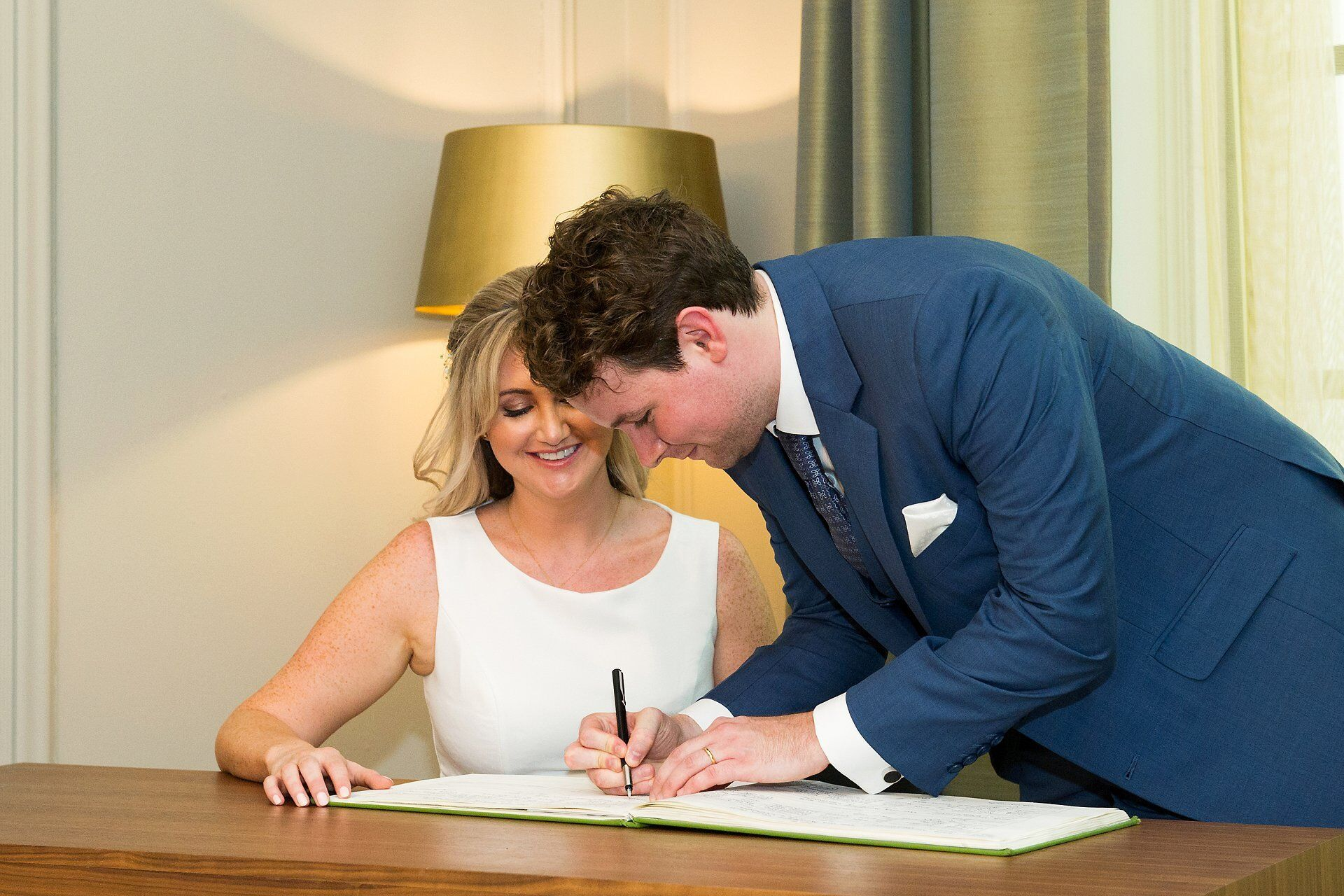 groom signs the official marriage register-at-westminster-register-office-watched-by-bride