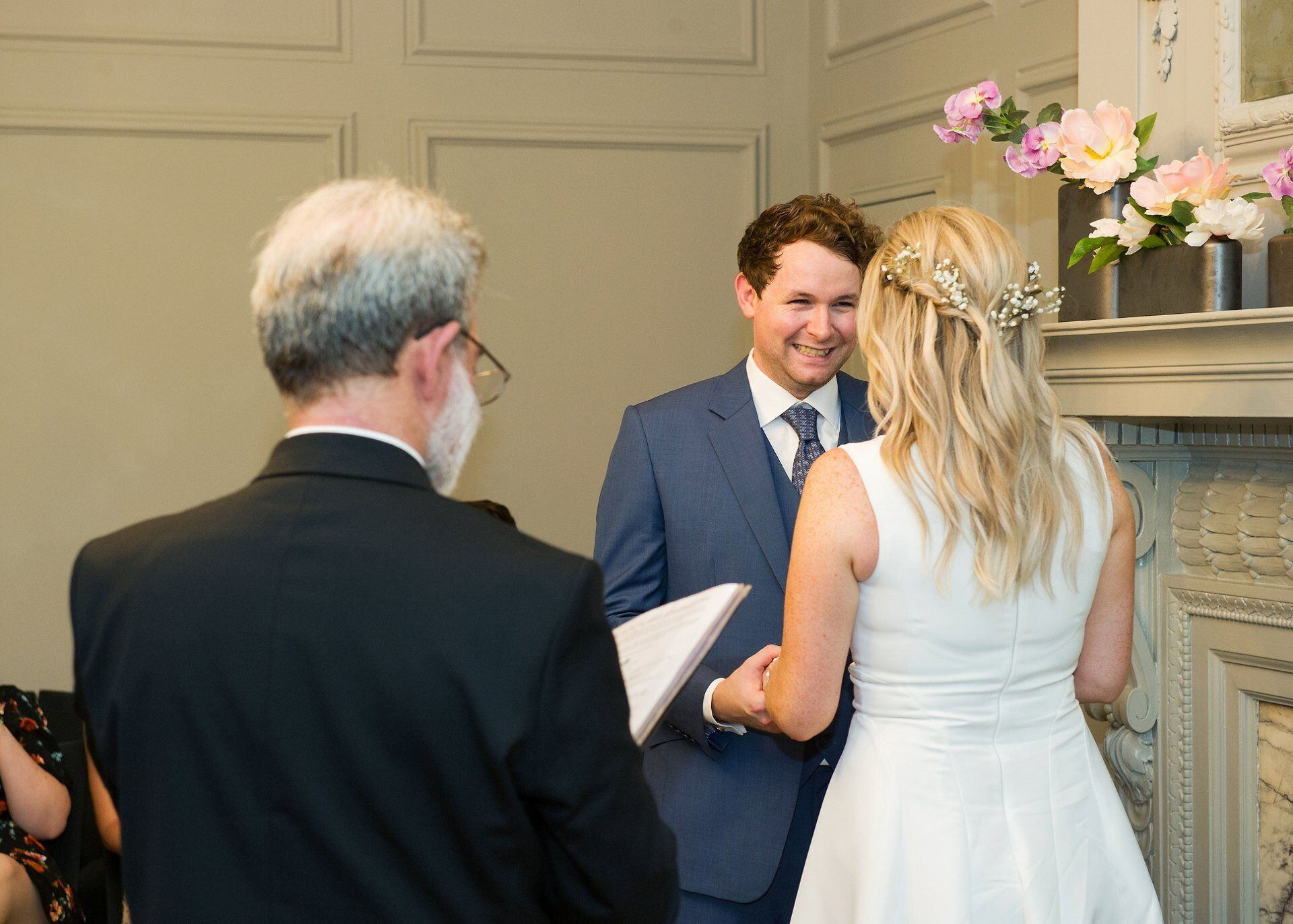 groom smiling at his bride in the soho room during their wedding vows
